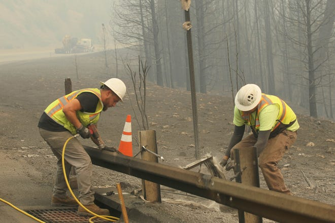 Brandon Harsh, left, and Garhett Parent, both Highway Specialty Co. workers repair a section of the guardrail the Delta Fire burned along I-5 south of Lamoine on Saturday afternoon, Sept. 8, 2018. (Hung T. Vu/ Special to the Record Searchlight)