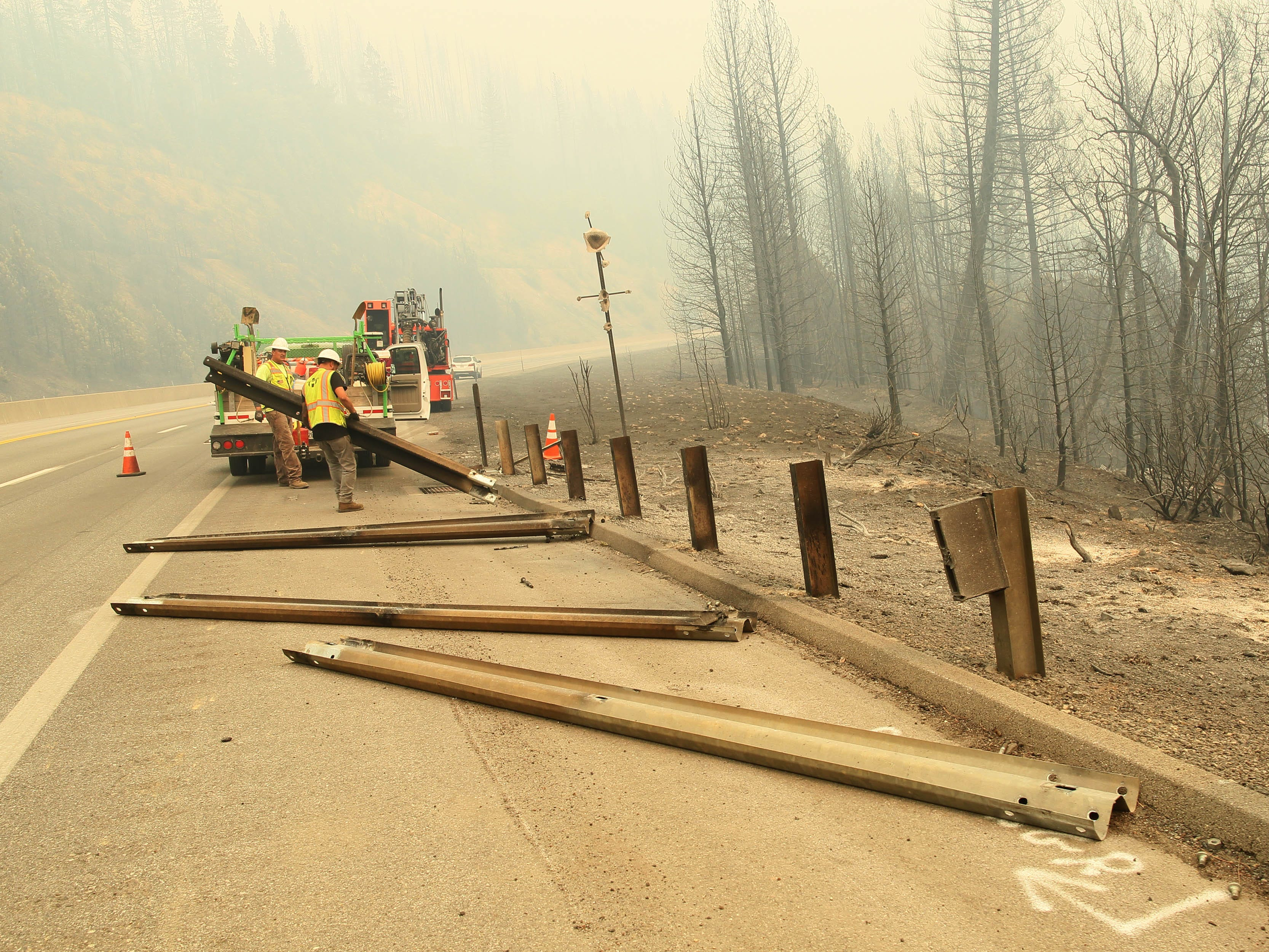 Highway Specialty Co. workers on Saturday afternoon, Sept. 8, 2018 repair a section of the rail where the Delta Fire burned out wooden posts on the guardrails along I-5 south of Lamoine. (Hung T. Vu/ Special to the Record Searchlight)