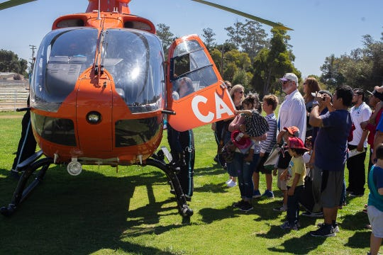 People lining up and taking pictures of the medical helicopter at the 5th Annual Touch-A-Truck event in the Salinas Sports Complex on Sunday, September 9, 2018.