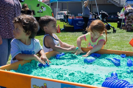 Kids playing with colored sand at the 5th Annual Touch-A-Truck event in the Salinas Sports Complex on Sunday, September 9, 2018.