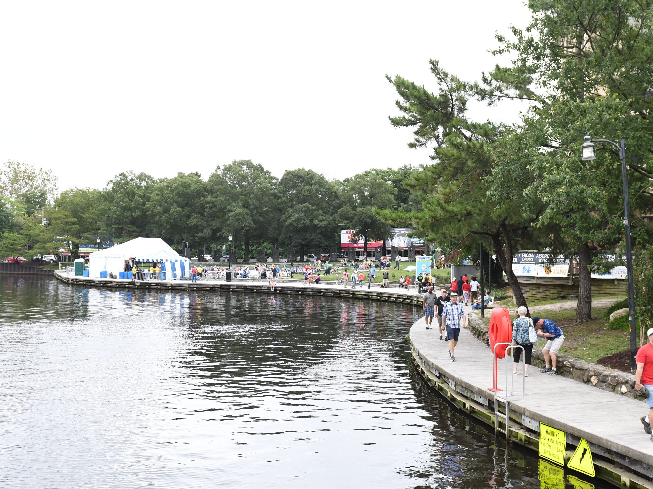 People stroll along the river walk in downtown Salisbury during the 78th National Folk Festival on Saturday, Sept. 8, 2018.