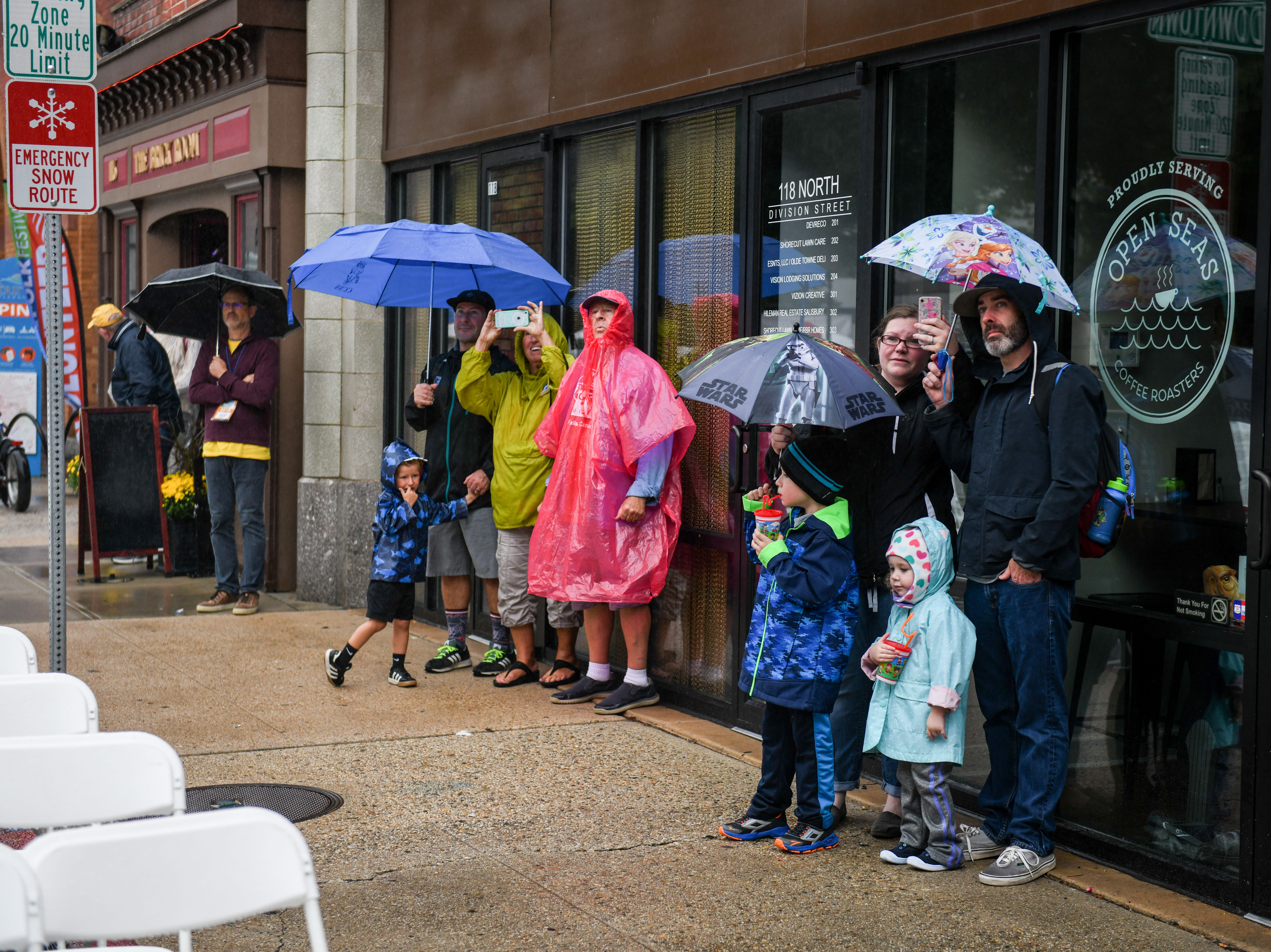 Attendees watch the Mangum & Company performance from the rain at the National Folk Fest in Salisbury on Sunday, Sept. 9.