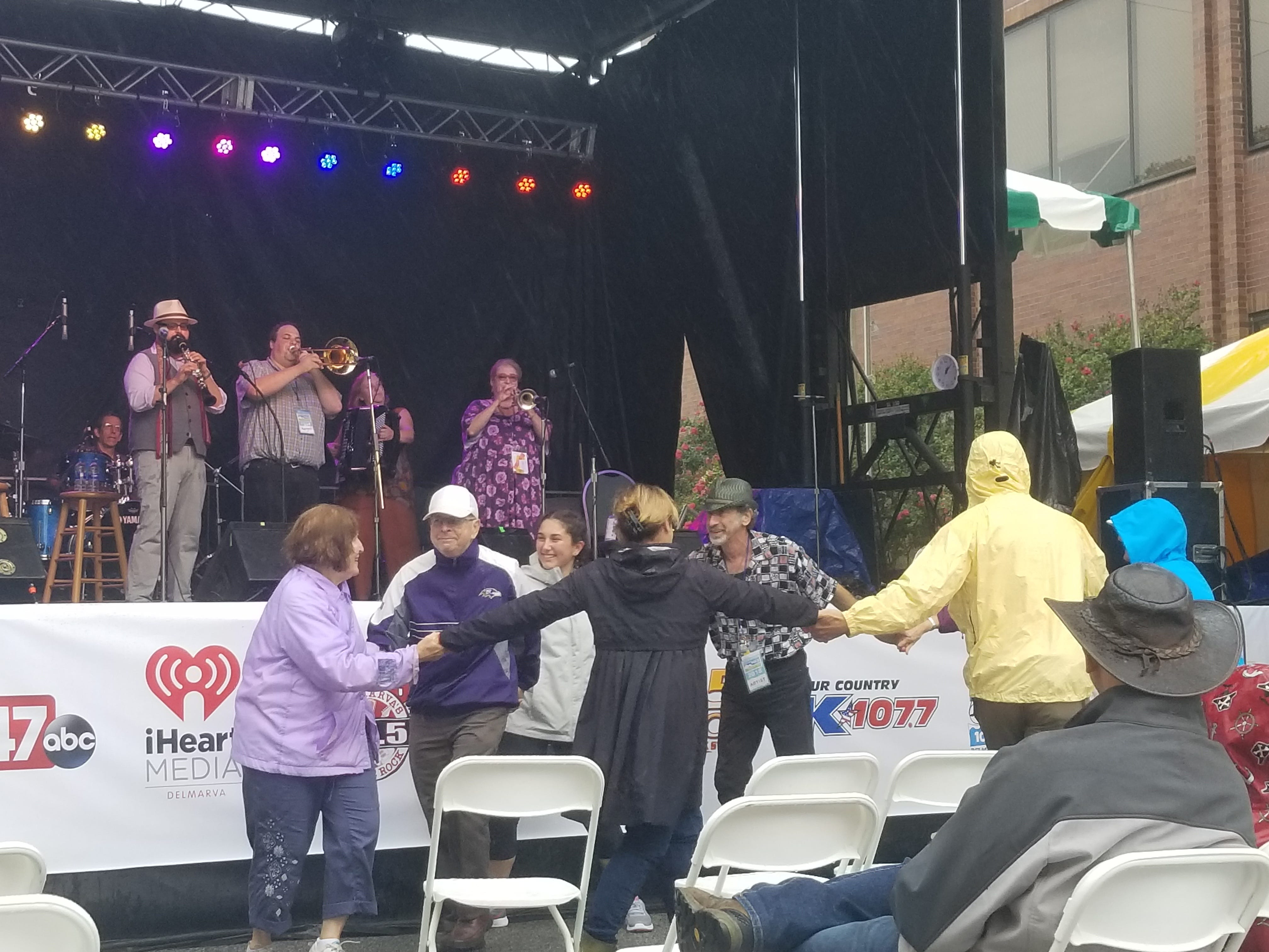 A dance party breaks out in the rain as Michael Winograd & the Honorable Mentshn perform Sunday, Sept. 9, 2018, at the National Folk Festival.