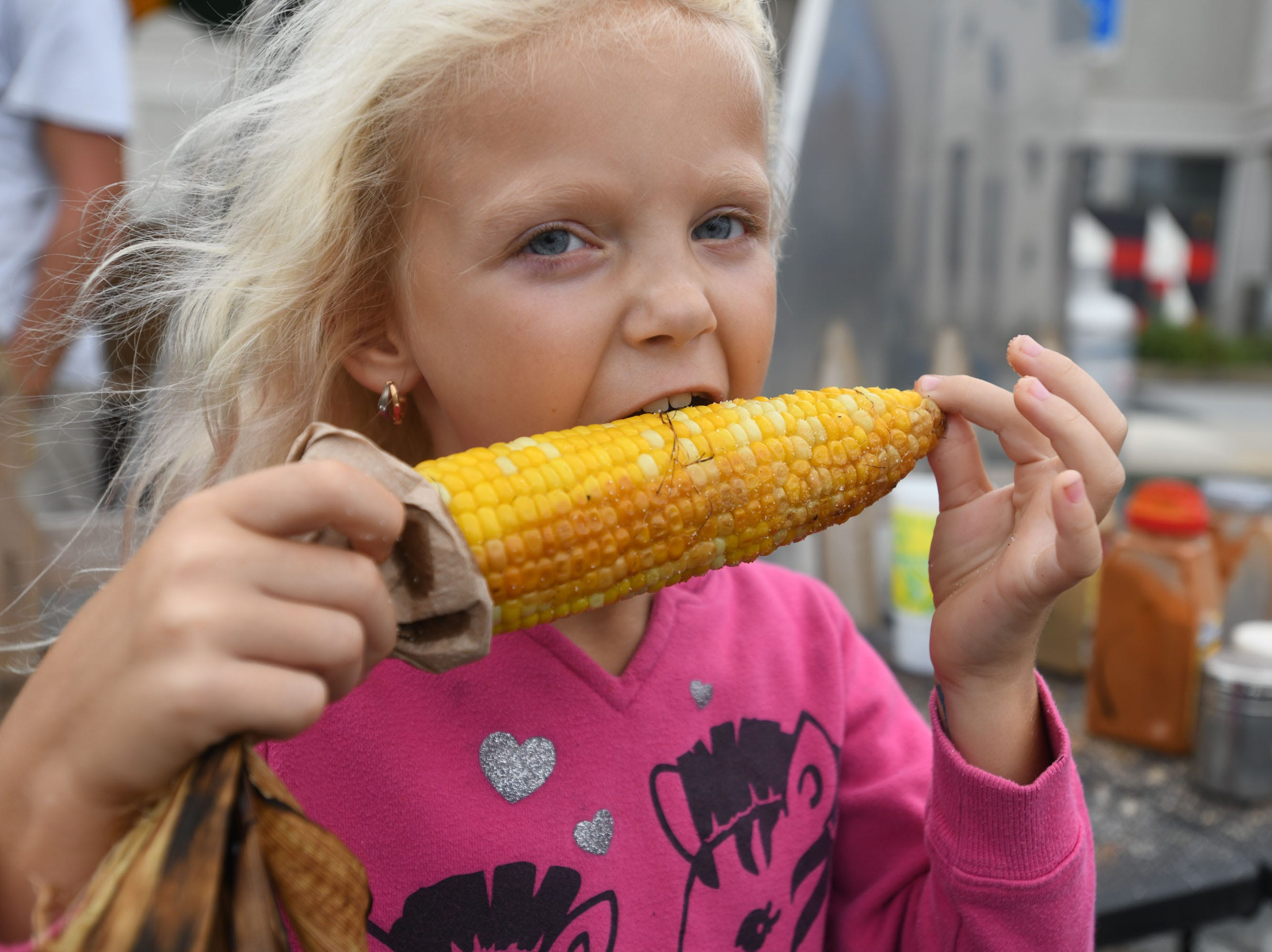 Katerina White, Delmar eats some roasted corn during the 78th National Folk Festival on Saturday, Sept. 8, 2018.