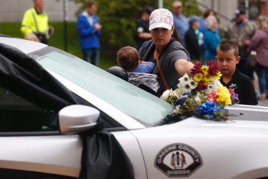 Shawnda Tuma along with her children Jayden, 8, and Addison, 1, lay flowers on the hood of a Greene County Sheriffs vehicle during a candlelight vigil for Deputy Aaron Roberts on Saturday, Sept. 8, 2018.