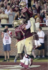 Florida State's Tamorrion Terry, top, is lifted in celebration by teammate Cole Minshew after scoring against Samford in the first quarter of an NCAA college football game, Saturday, Sept. 8, 2018, in Tallahassee Fla.