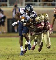 Samford Bulldogs wide receiver Kelvin McKnight (6) carries defenders as the Florida State Seminoles host the Samford Bulldogs at Doak Campbell Stadium.