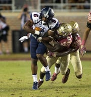 Samford Bulldogs wide receiver Kelvin McKnight (6) carries defenders as the Florida State Seminoles host the Samford Bulldogs at Doak Campbell Stadium.