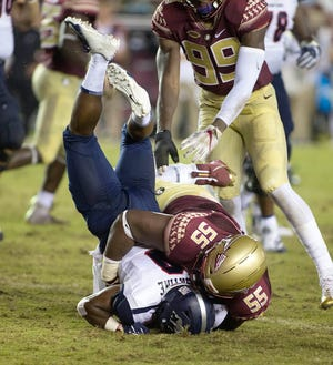 Florida State Seminoles defensive tackle Fredrick Jones (55) slams Samford Bulldogs wide receiver Moise Satine (9) during the second quarter of play as the Florida State Seminoles host the Samford Bulldogs at Doak Campbell Stadium.
