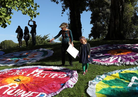 Natalie Levine, of Los Angeles, talks to her granddaughter, Sonia Kupersztoch, 5, of Oakland, as they look at parachutes during the Rise for Climate, Jobs, and Justice rally at Embarcadero Plaza on Saturday, Sept. 8, 2018, in San Francisco. Thousands are expected to march through the streets of San Francisco, just days before the Global Climate Action Summit next week. (Yalonda M. James/San Francisco Chronicle via AP)
