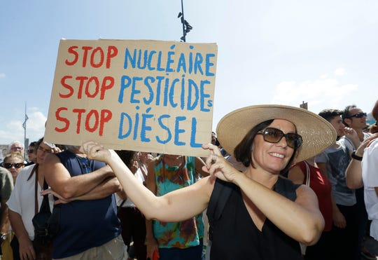"A woman holds a placard reading ""Stop nuclear, Stop pesticides, Stop diesel"", during a demonstration for the climate in Marseille, southern France, Saturday, Sept. 8, 2018. Demonstrators in cities across France and Europe are marching on Saturday as part of a global day of protest ahead of a climate action summit this month in San Francisco, USA. (AP Photo/Claude Paris)"