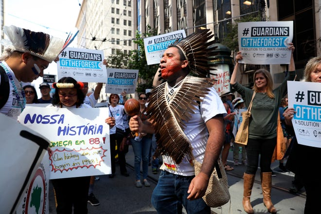 Dinamam Tux', with Articulation of Indigenous Peoples of Brazil (APIB) chants as he participates in the Rise for Climate, Jobs, and Justice march on Market Street on Saturday, Sept.8, 2018, in San Francisco. Thousands marched through the streets of San Francisco, just days before the Global Climate Action Summit next week. (Yalonda M. James/San Francisco Chronicle via AP)