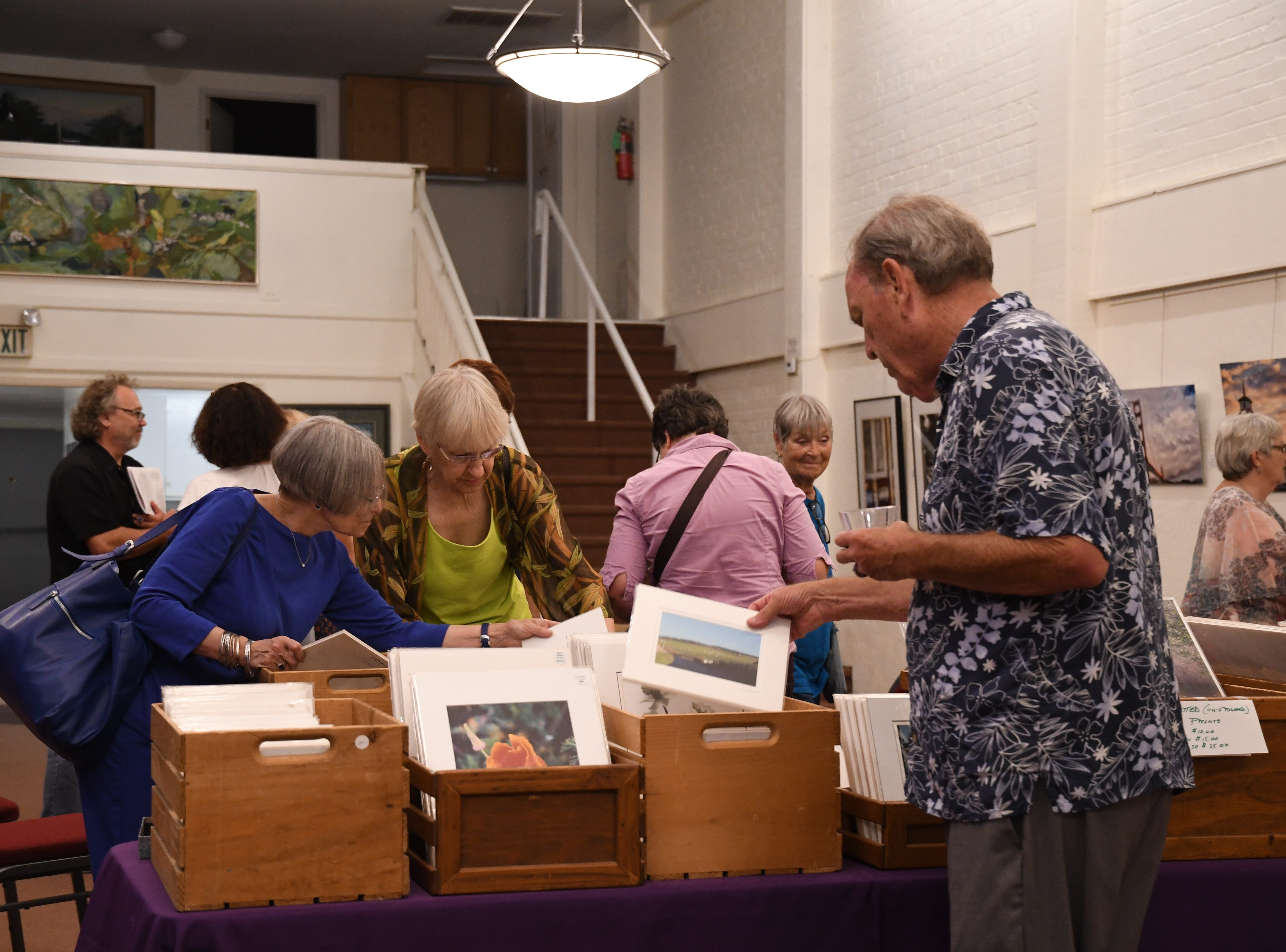 Photographer Ginny Wilson selling her collection of matted photos at Brandon Mitchell Gallery