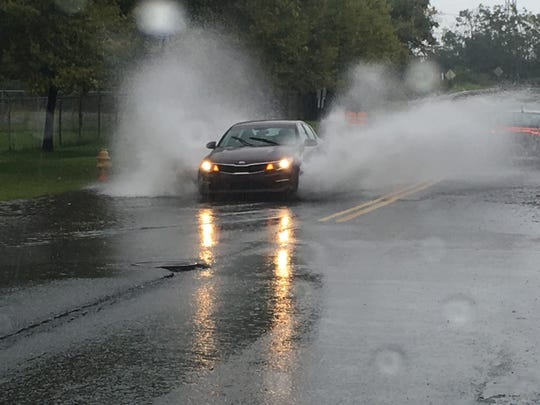 A car drives through pooling water on 12th Street near I-495 in Delaware Sunday.