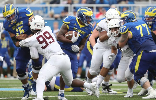 Delaware's Kani Kane has a hole courtesy Noah Beh (left) and Mario Farinella in the third quarter of the Blue Hens' 37-0 win at Delaware Stadium Saturday.