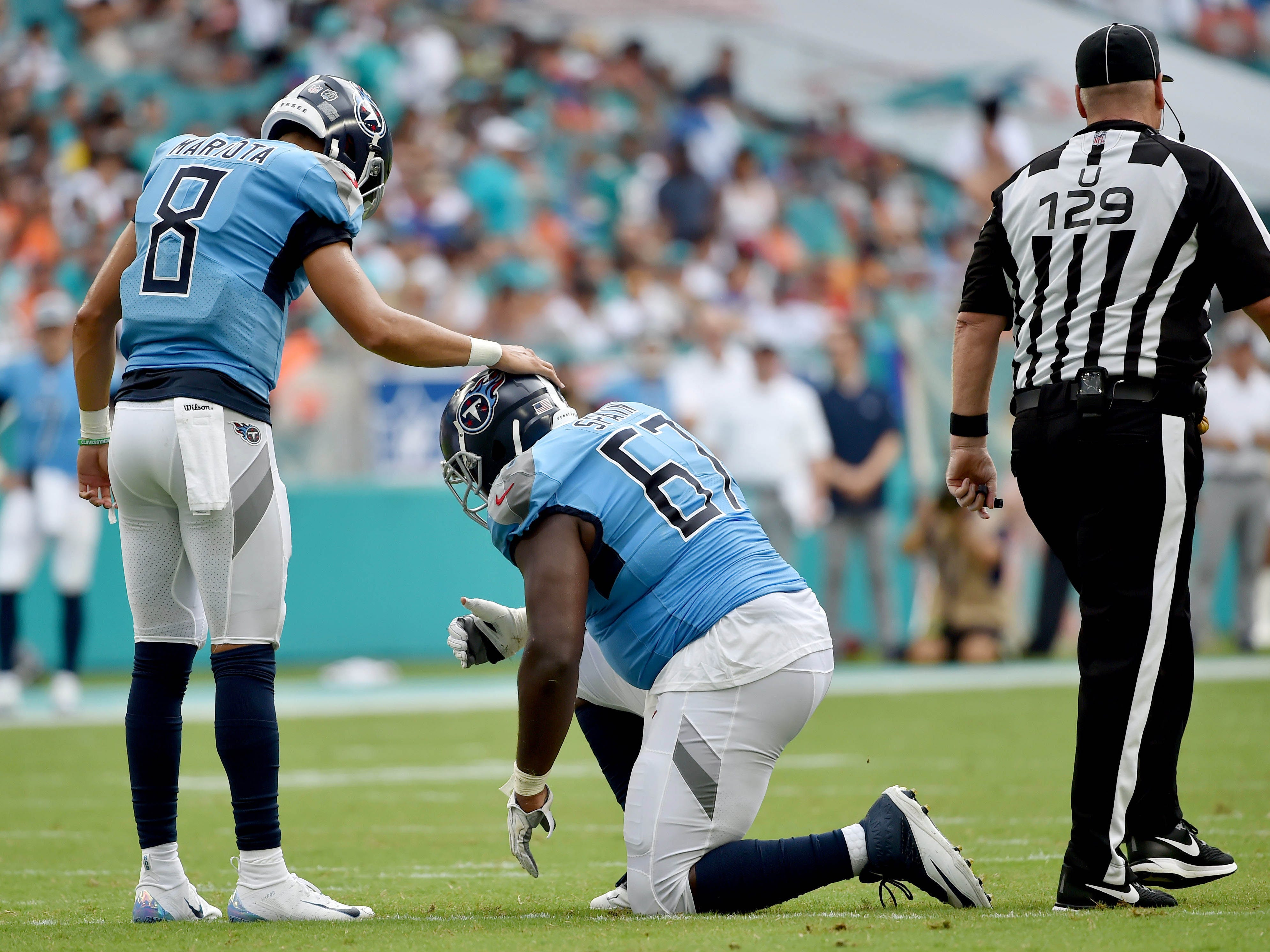 Tennessee Titans quarterback Marcus Mariota checks on the condition of Titans offensive guard Quinton Spain during the first half against the Miami Dolphins at Hard Rock Stadium.