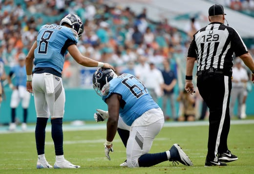 Tennessee Titans quarterback Marcus Mariota checks on the condition of Titans offensive guard Quinton Spain during the first half against the Miami Dolphins at Hard Rock Stadium. - Packers QB Carted Off In Clash With Bears