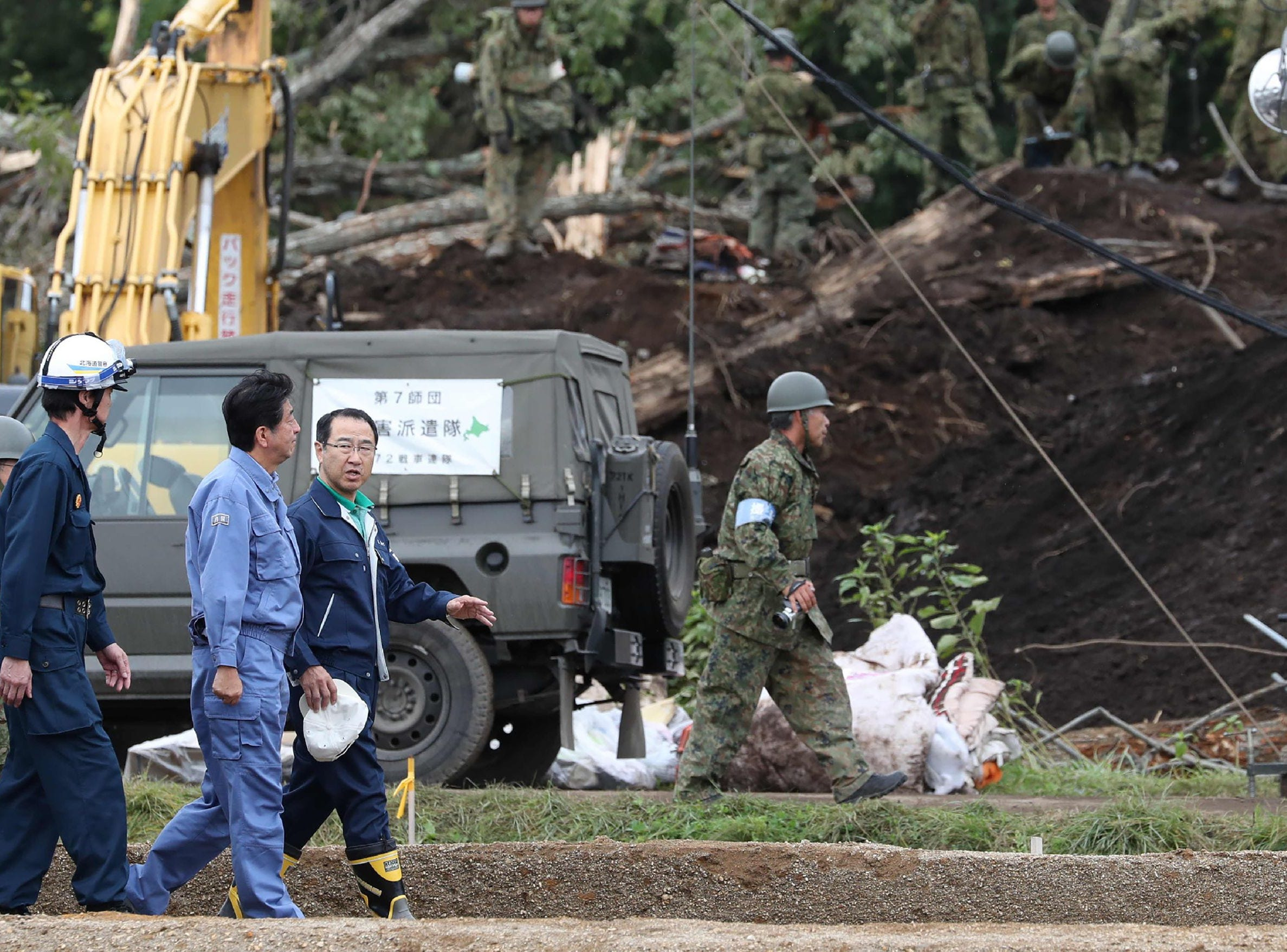 Japanese Prime Minister Shinzo Abe, second from left, visits the devastated city of Astuma on Sept. 9, 2018 after a 6.6-magnitude earthquake hit the northern Japanese island of Hokkaido on September 6. Abe visited the quake-hit northern region of Hokkaido as officials confirmed two more deaths bringing the toll to 37.