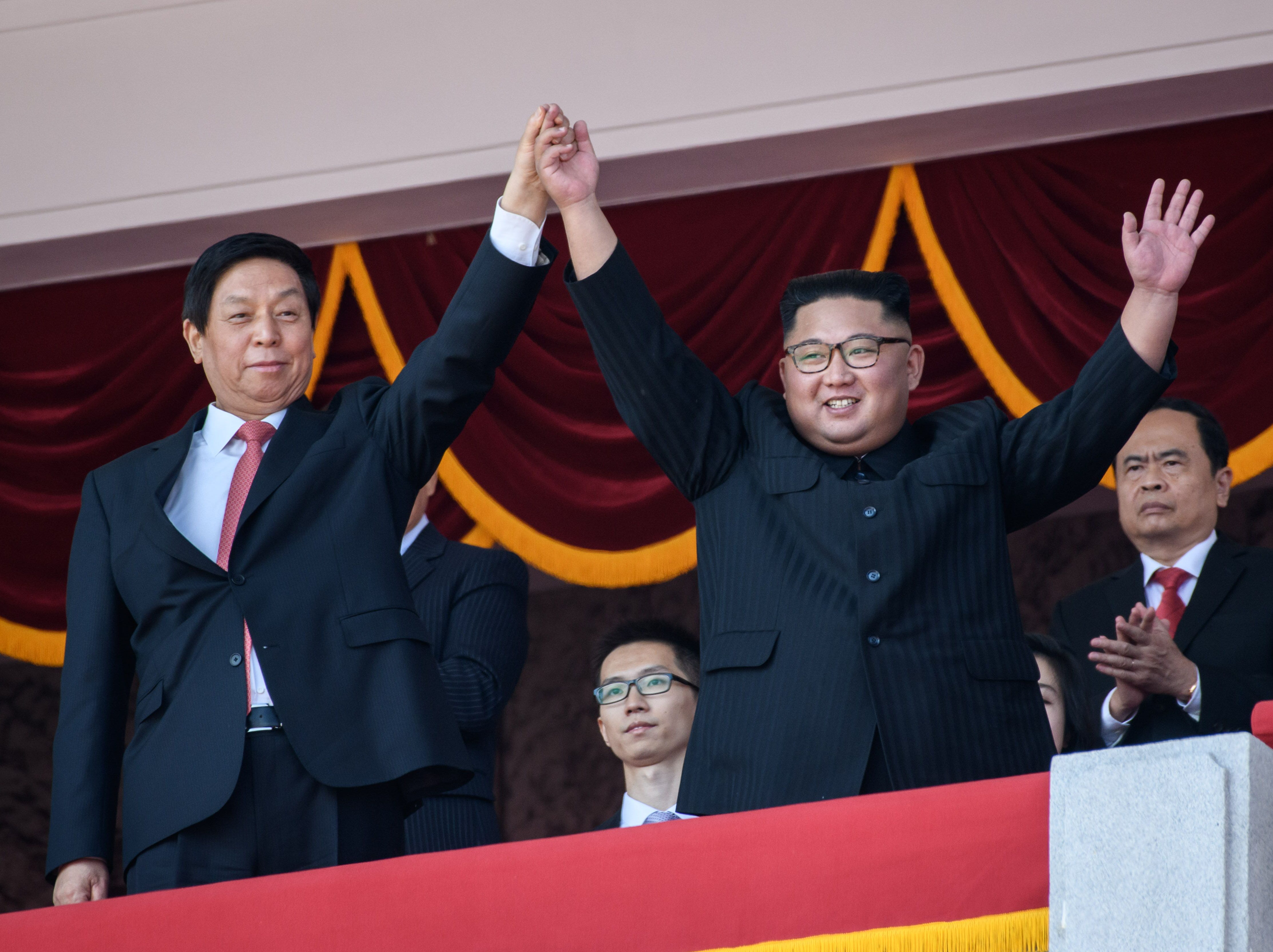 North Korea's leader Kim Jong Un, right, waves with China's Chairman of the Standing Committee of the National People's Congress Li Zhanshu from a balcony of the Grand People's House on Kim Il Sung square following military parade and mass rally on Sept. 9, 2018.