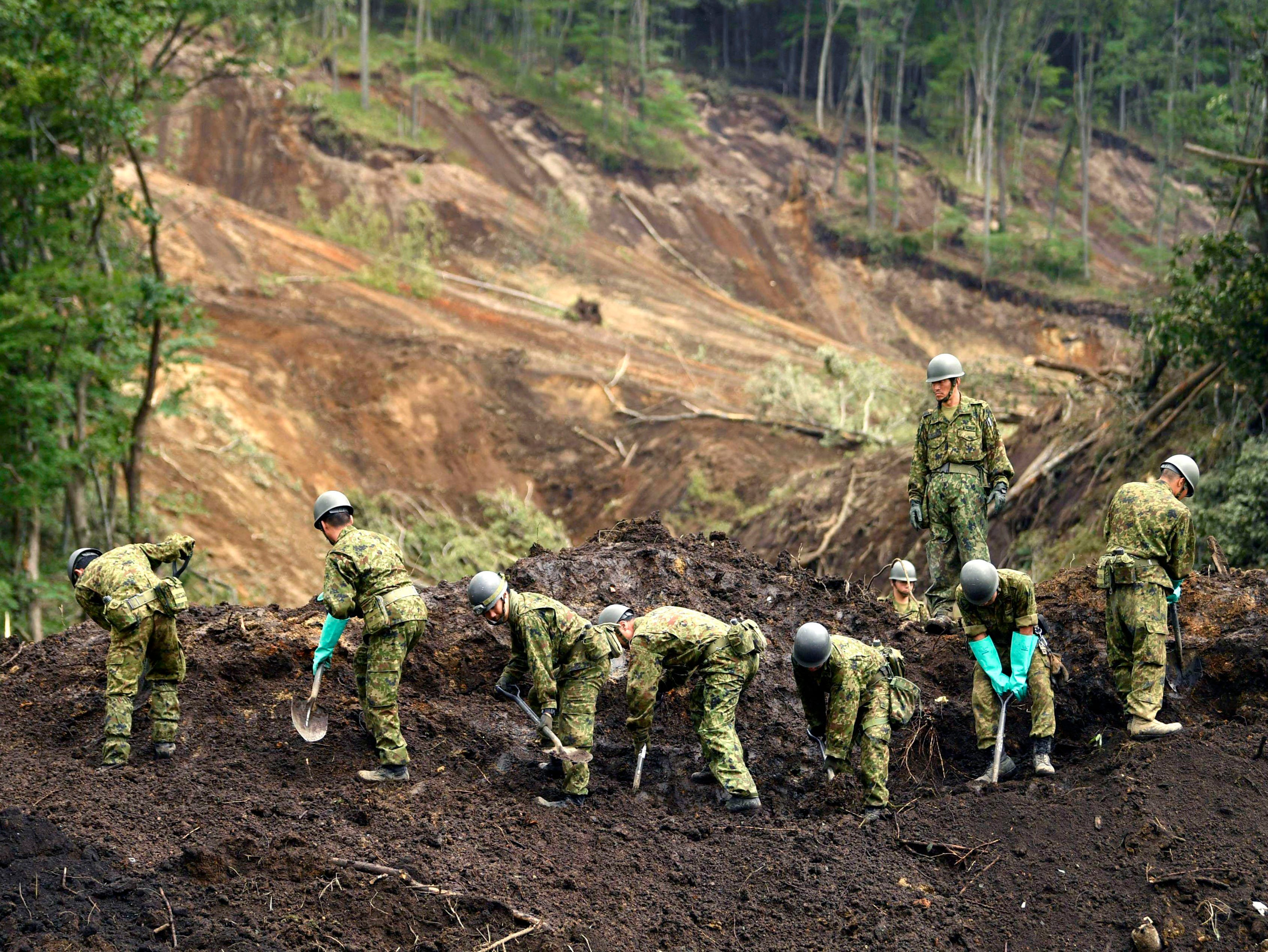 Japan's Self-Defense Force members work at the site of a landslide triggered by Thursday's earthquake in Atsuma, Hokkaido, northern Japan Sunday, Sept. 9, 2018.