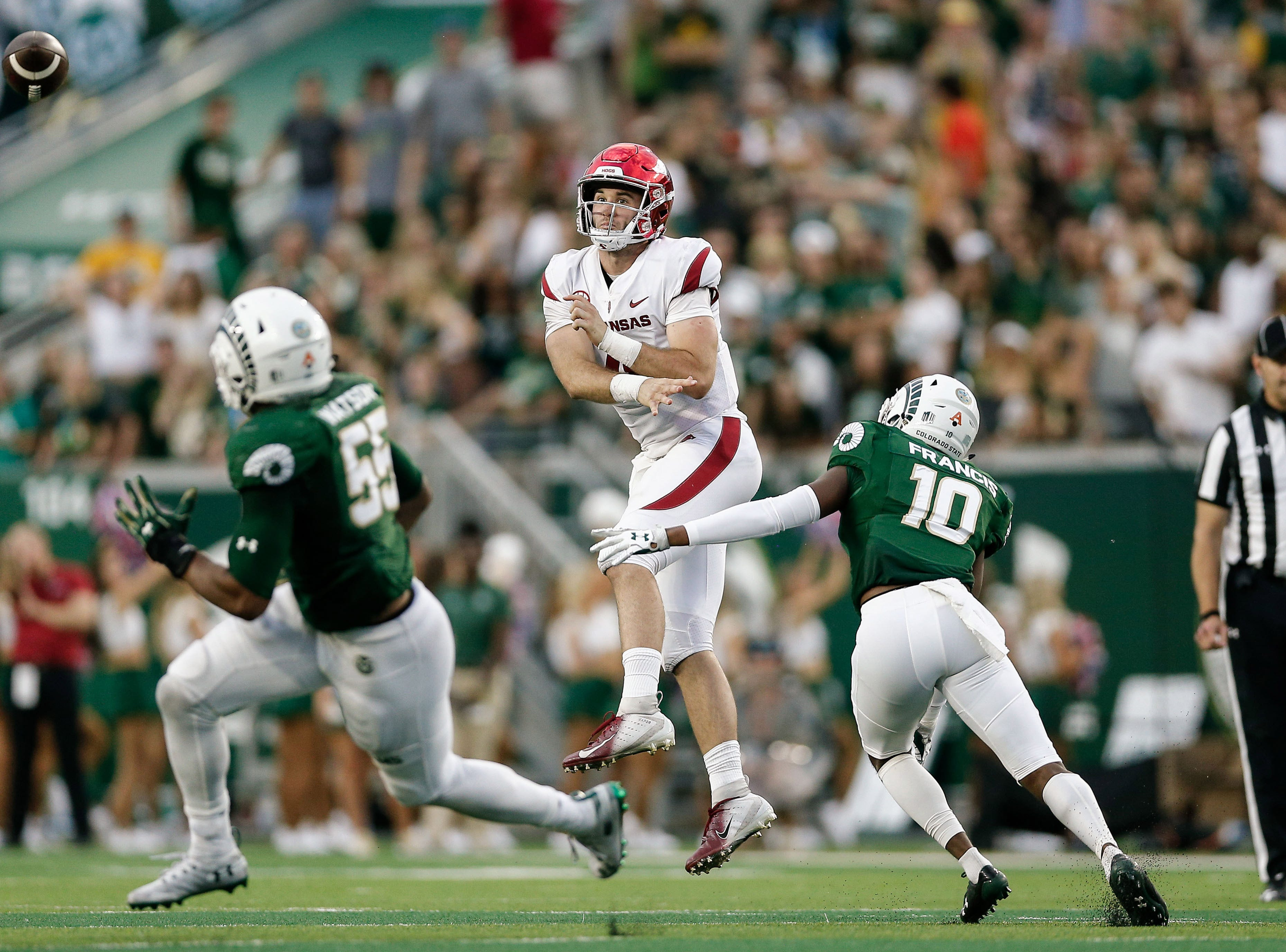 Arkansas Razorbacks quarterback Ty Storey (4) passes the ball under pressure from Colorado State Rams safety Tywan Francis (10) as linebacker Josh Watson (55) defends in the second quarter at Canvas Stadium.