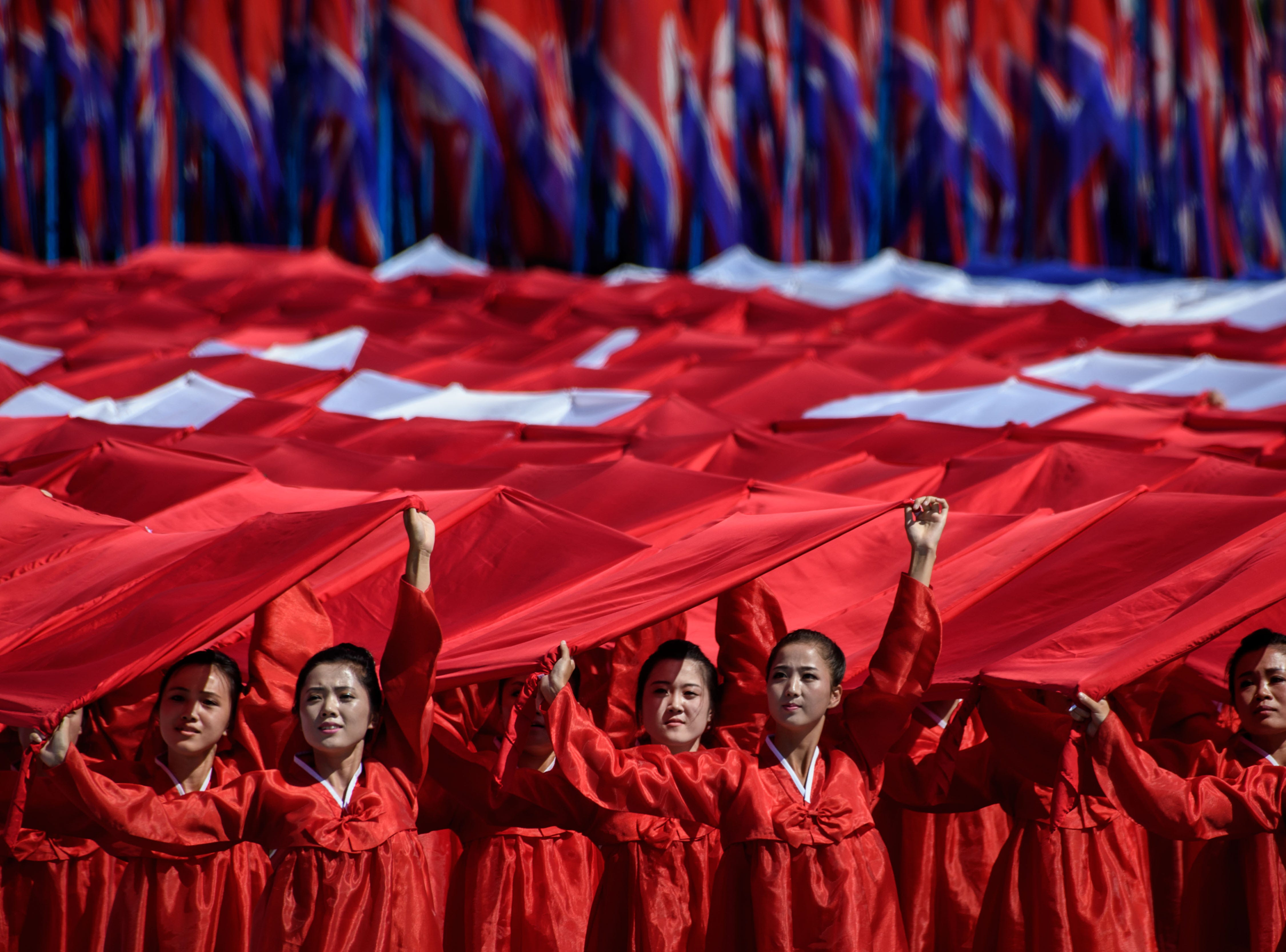 Participants march past a balcony from where North Korea's leader Kim Jong Un was watching, during a mass rally on Kim Il Sung square in Pyongyang on Sept. 9, 2018.