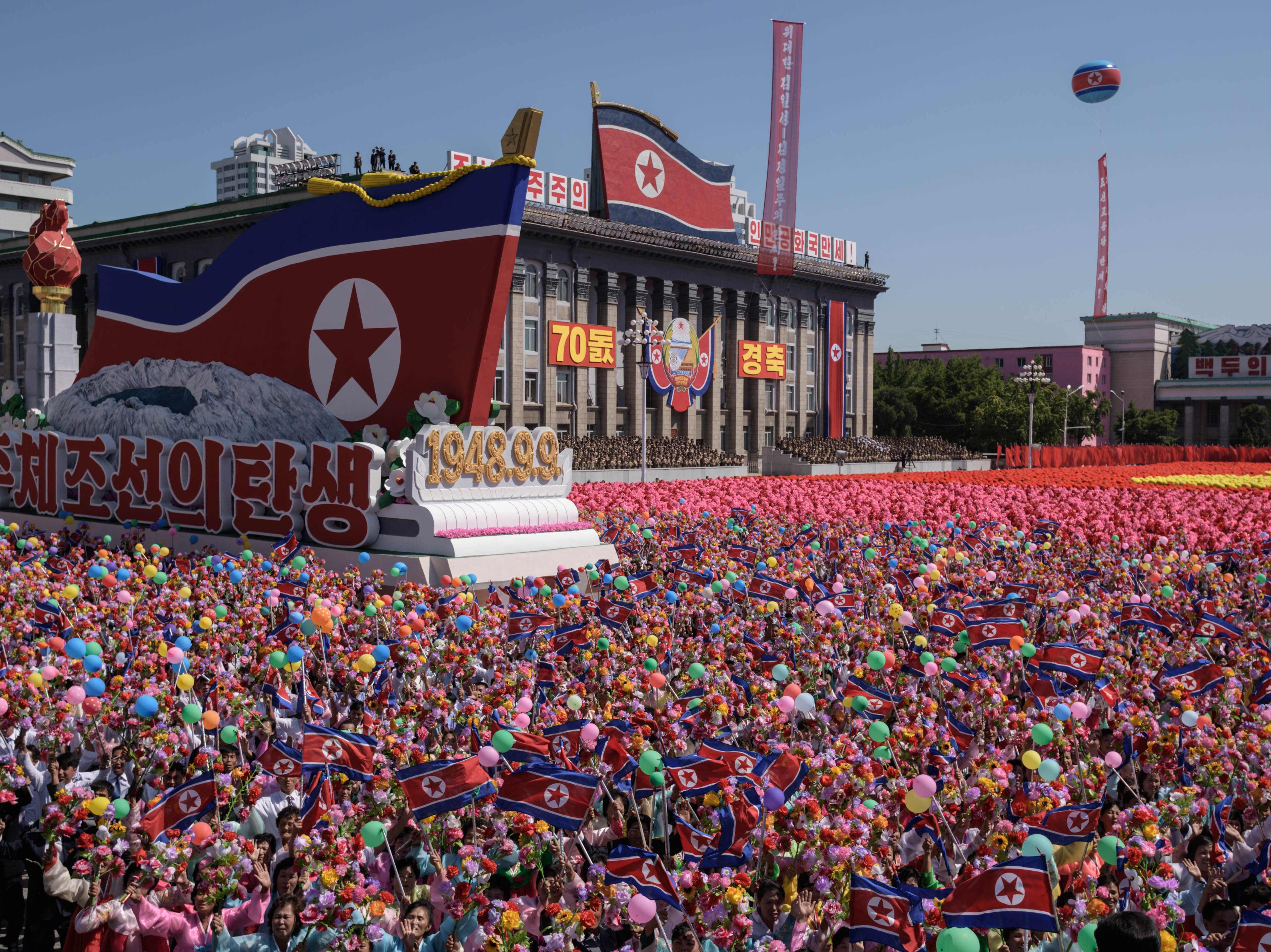 Participants wave flowers as they march past a balcony from where North Korea's leader Kim Jong Un was watching, during a mass rally on Kim Il Sung square in Pyongyang on Sept. 9, 2018. North Korea held a military parade to mark its 70th birthday, but refrained from showing off the intercontinental ballistic missiles that have seen it hit with multiple international sanctions.