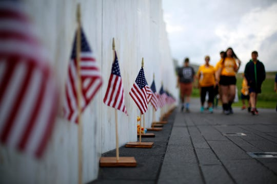 Visitors to the Flight 93 National Memorial pause at the Wall of Names containing the names of the 40 passengers and crew of United Flight 93 that were killed in this field in Shanksville, Pa., on May 31, 2018.