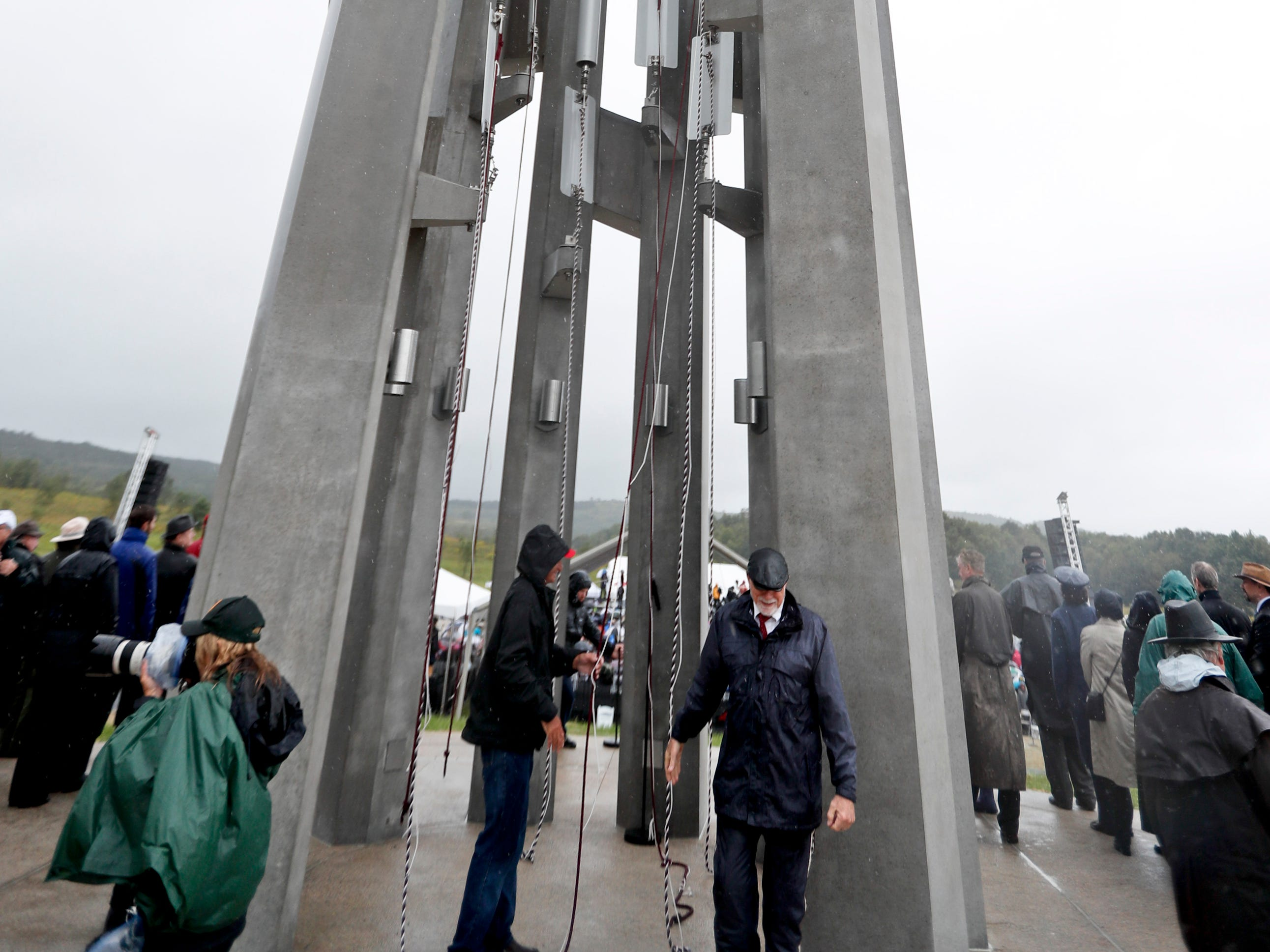 Members of the families of passengers of Flight 93, and friends and family reperesentatives stand under the 93-foot tall Tower of Voices after the dedication on Sunday, Sept. 9, 2018 at the Flight 93 National Memorial in Shanksville, Pa.