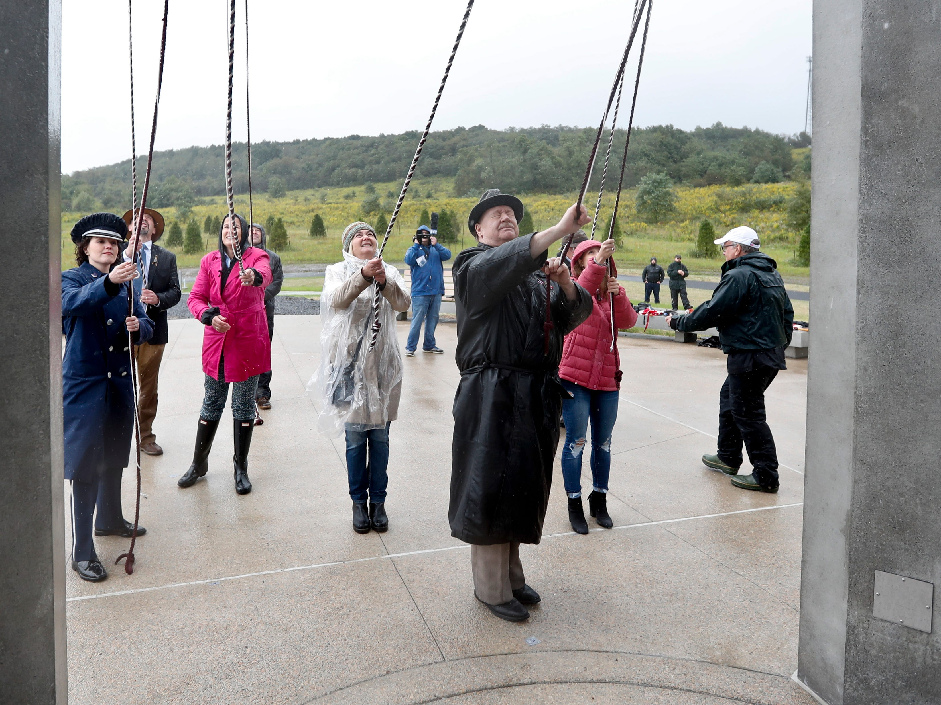 Members of passenger families, friends and volunteer representatives, pull the ropes to ring the chimes at the dedication of the 93-foot tall Tower of Voices on Sunday, Sept. 9, 2018 at the Flight 93 National Memorial in Shanksville, Pa. The tower contains 40 wind chimes representing the 40 people that perished in the crash of Flight 93 in the terrorist attacks of Sept. 11, 2001.