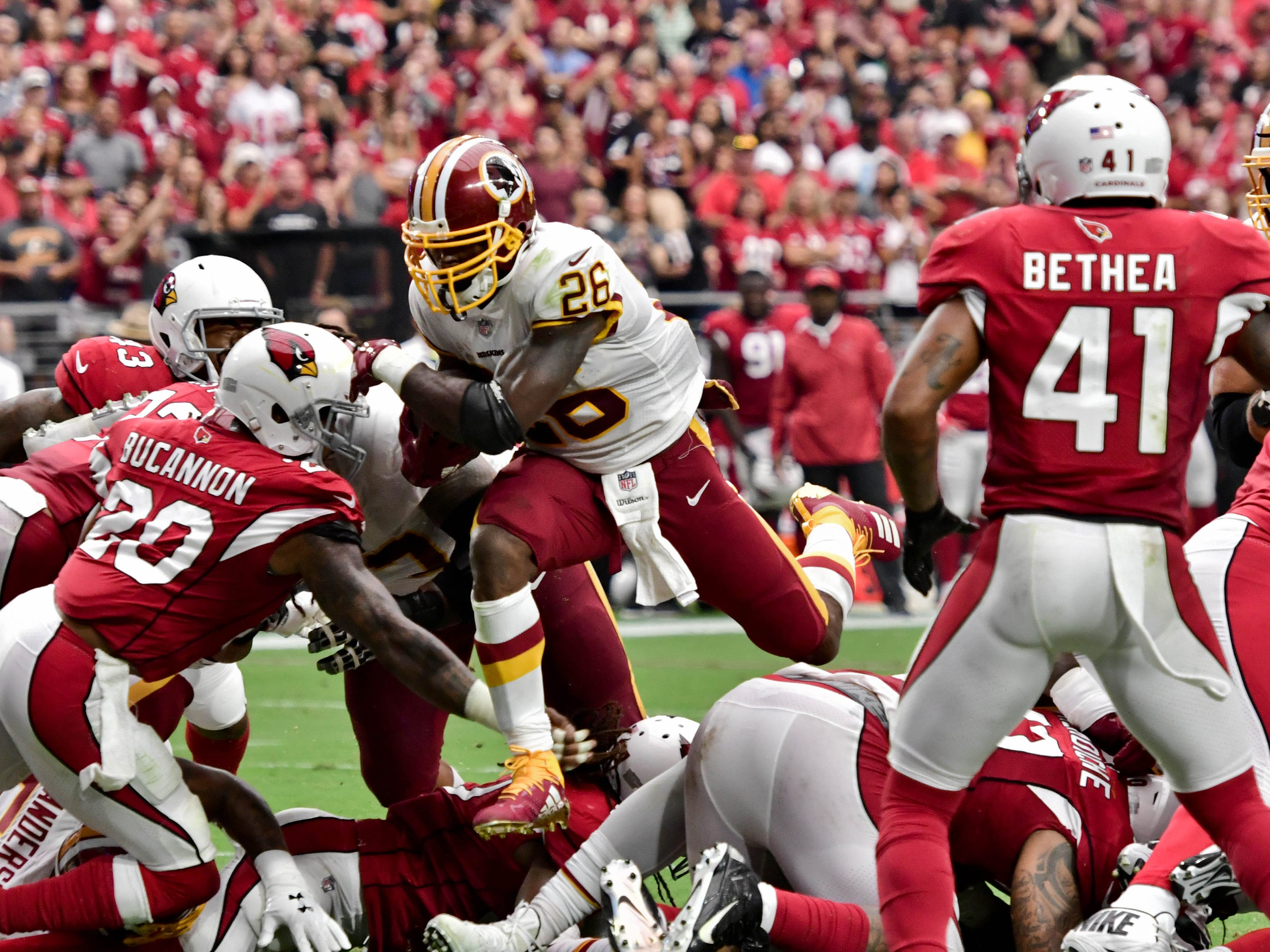 Sep 9, 2018; Glendale, AZ, USA; Washington Redskins running back Adrian Peterson (26) leaps over Arizona Cardinals defenders to score a touchdown in the first half at State Farm Stadium. Mandatory Credit: Matt Kartozian-USA TODAY Sports