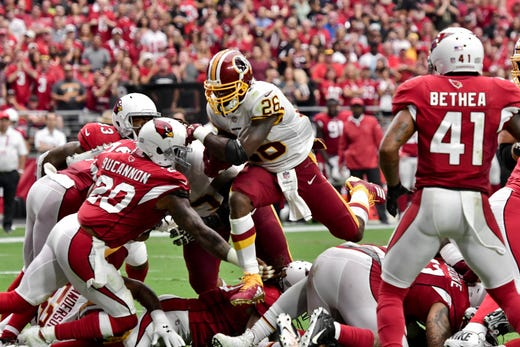 Sep 9, 2018; Glendale, AZ, USA; Washington Redskins running back Adrian Peterson (26) leaps over Arizona Cardinals defenders to score a touchdown in the first half at State Farm Stadium. Mandatory Credit: Matt Kartozian-USA TODAY Sports - Packers QB Carted Off In Clash With Bears