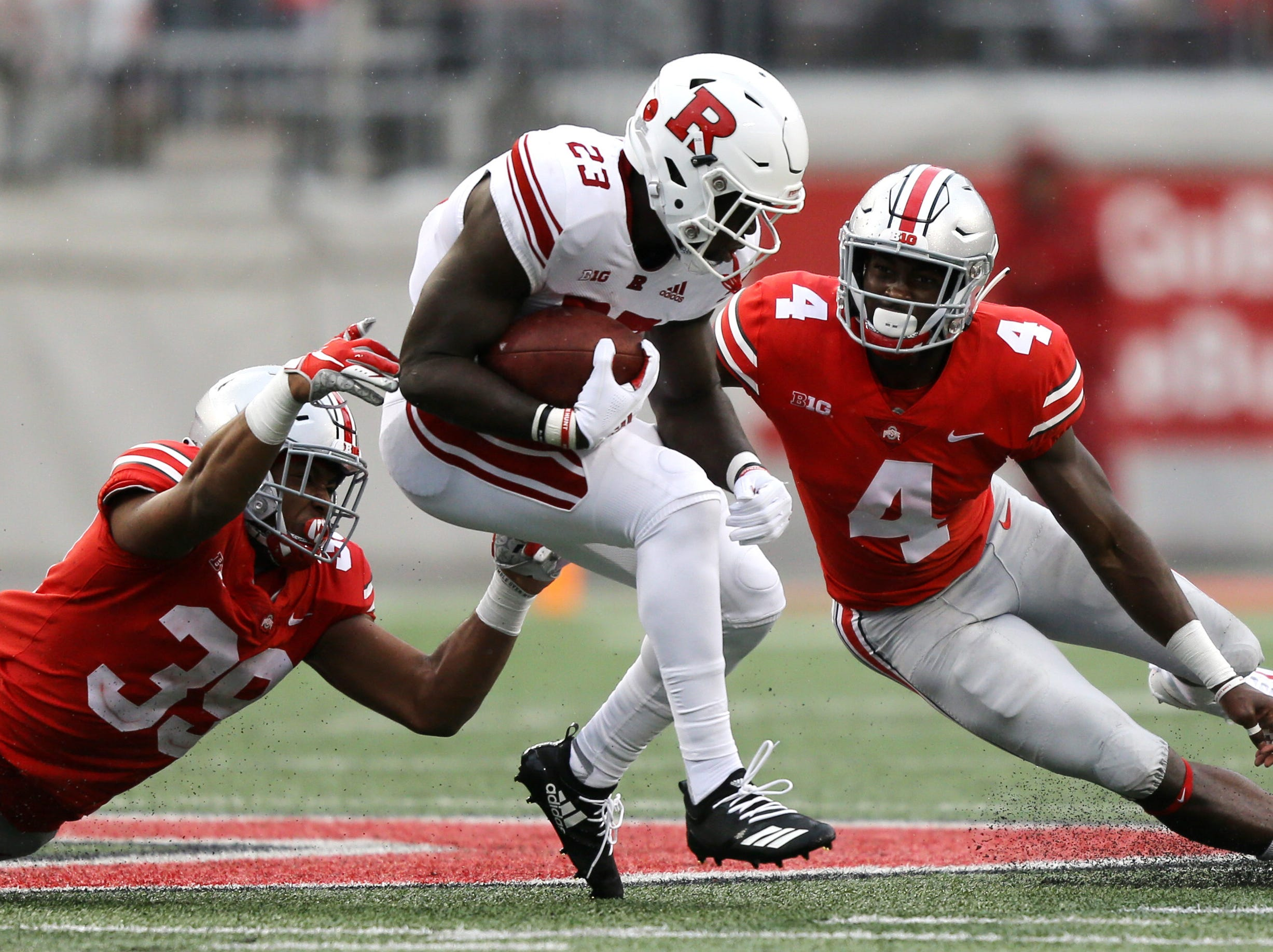 Rutgers Scarlet Knights running back Jonathan Hilliman (23) carries the ball against Ohio State Buckeyes linebacker Malik Harrison (39) and safety Jordan Fuller (4) in the second half at Ohio Stadium.