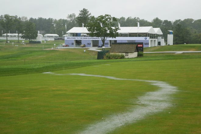 A stream of rain water runs down the 18th fairway during a weather delay prior to the final round of the BMW Championship at Aronimink Golf Club.