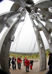 In this photo made with a fisheye lens, former Pennsylvania governor Tom Ridge and family, friends and others listen to the first ringing of the chimes at the dedication of the Tower of Voices on  Sept. 9, 2018, at the Flight 93 National Memorial in Shanksville, Pa.