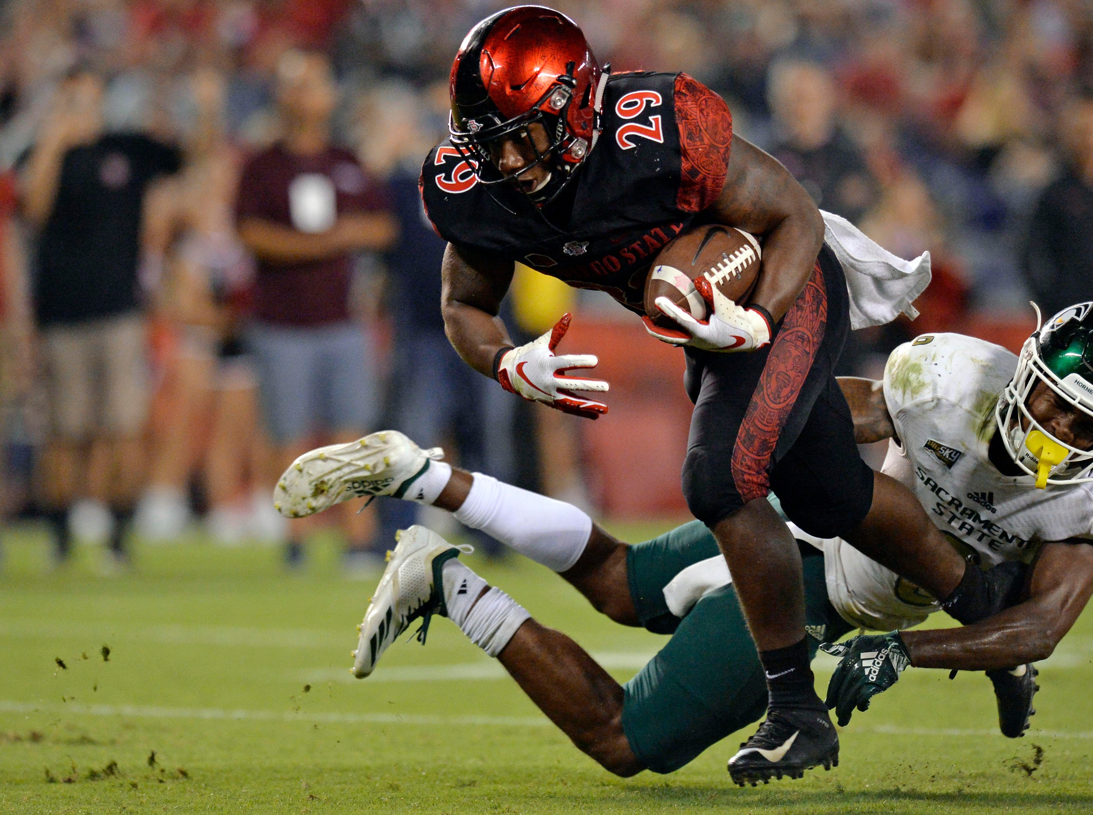 San Diego State Aztecs running back Juwan Washington (29) scores a fourth-quarter touchdown as Sacramento State Hornets defensive back Caelan Barnes (8) defends at SDCCU Stadium.