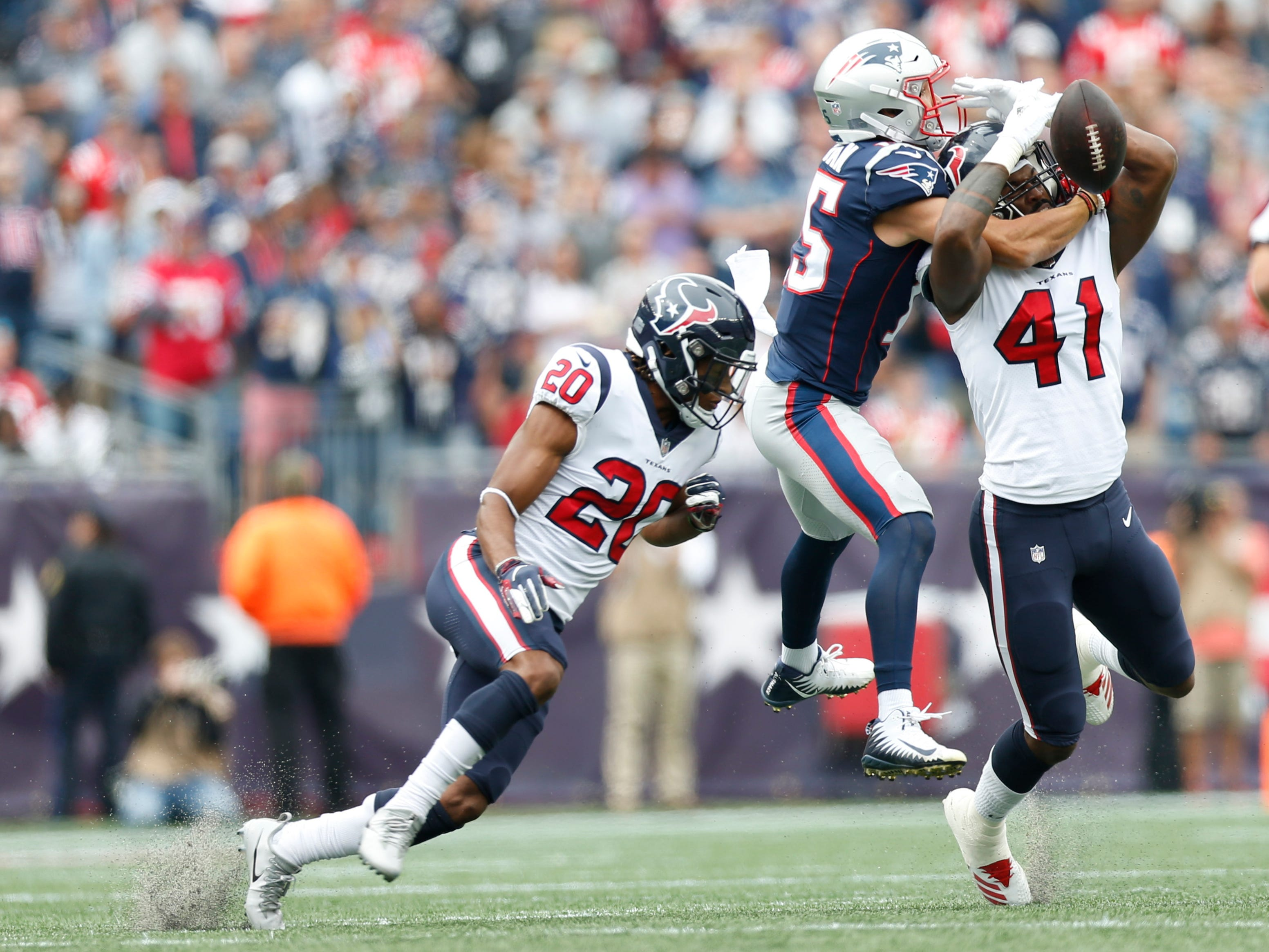 Houston Texans linebacker Zach Cunningham breaks up a pass intended for New England Patriots wide receiver Chris Hogan with the help of defensive back Justin Reid during the second quarter at Gillette Stadium.