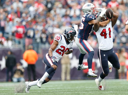 Houston Texans linebacker Zach Cunningham breaks up a pass intended for New England Patriots wide receiver Chris Hogan with the help of defensive back Justin Reid during the second quarter at Gillette Stadium. - Packers QB Carted Off In Clash With Bears