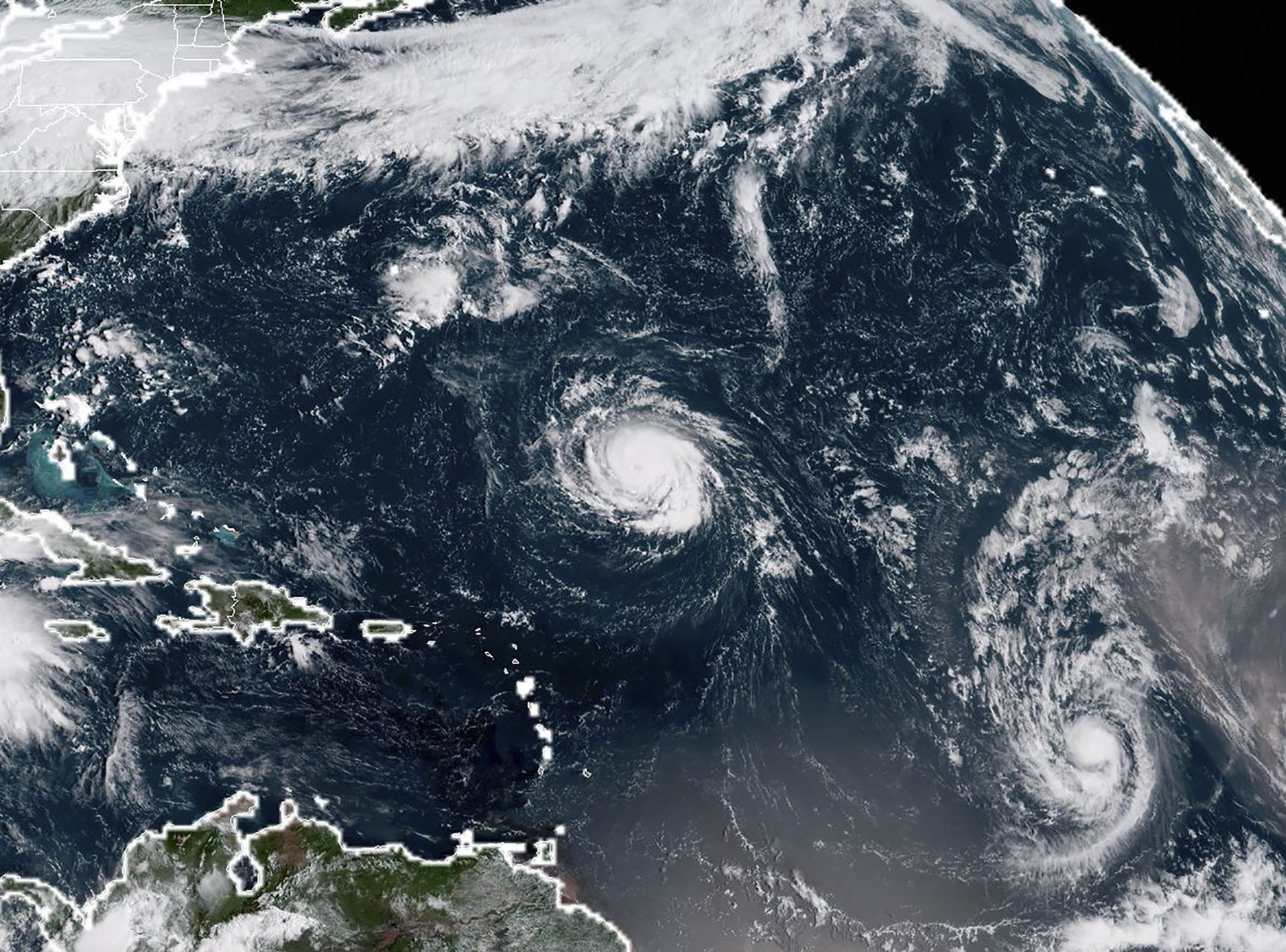 This NOAA/RAMMB satellite image taken at 13:30 UTC on September 9, 2018, shows (L-R) Tropical Storm Florence, Tropical Storm Isaac and Tropical Storm Helene in the Atantic Ocean.