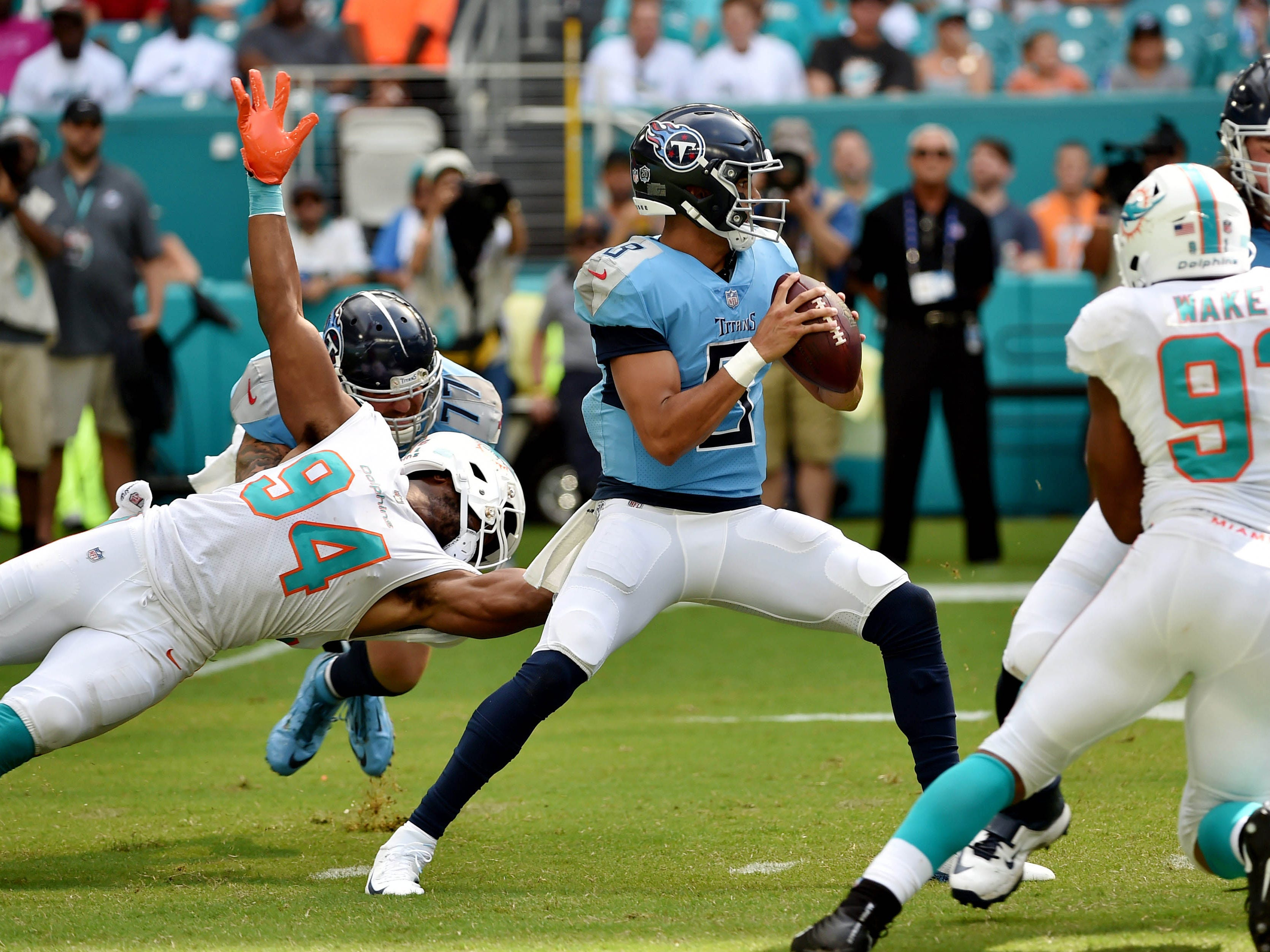 Sep 9, 2018; Miami Gardens, FL, USA; Tennessee Titans quarterback Marcus Mariota (8) throws a pass as Miami Dolphins defensive end Robert Quinn (94) has his facemask pulled on by Tennessee Titans offensive tackle Taylor Lewan (77) during the first half at Hard Rock Stadium. Mandatory Credit: Steve Mitchell-USA TODAY Sports
