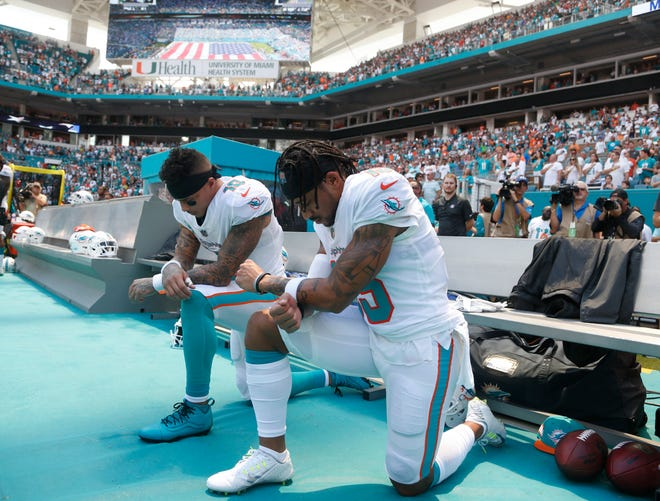 Miami Dolphins wide receiver Kenny Stills (10) and Miami Dolphins wide receiver Albert Wilson (15) kneel during the national anthem before an NFL football game against the Tennessee Titans, Sunday, Sept. 9, 2018, in Miami Gardens, Fla.