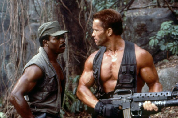 "Dillon (Carl Weathers, left) and Dutch (Arnold Schwarzenegger) deal with a vexing jungle threat in ""Predator."""