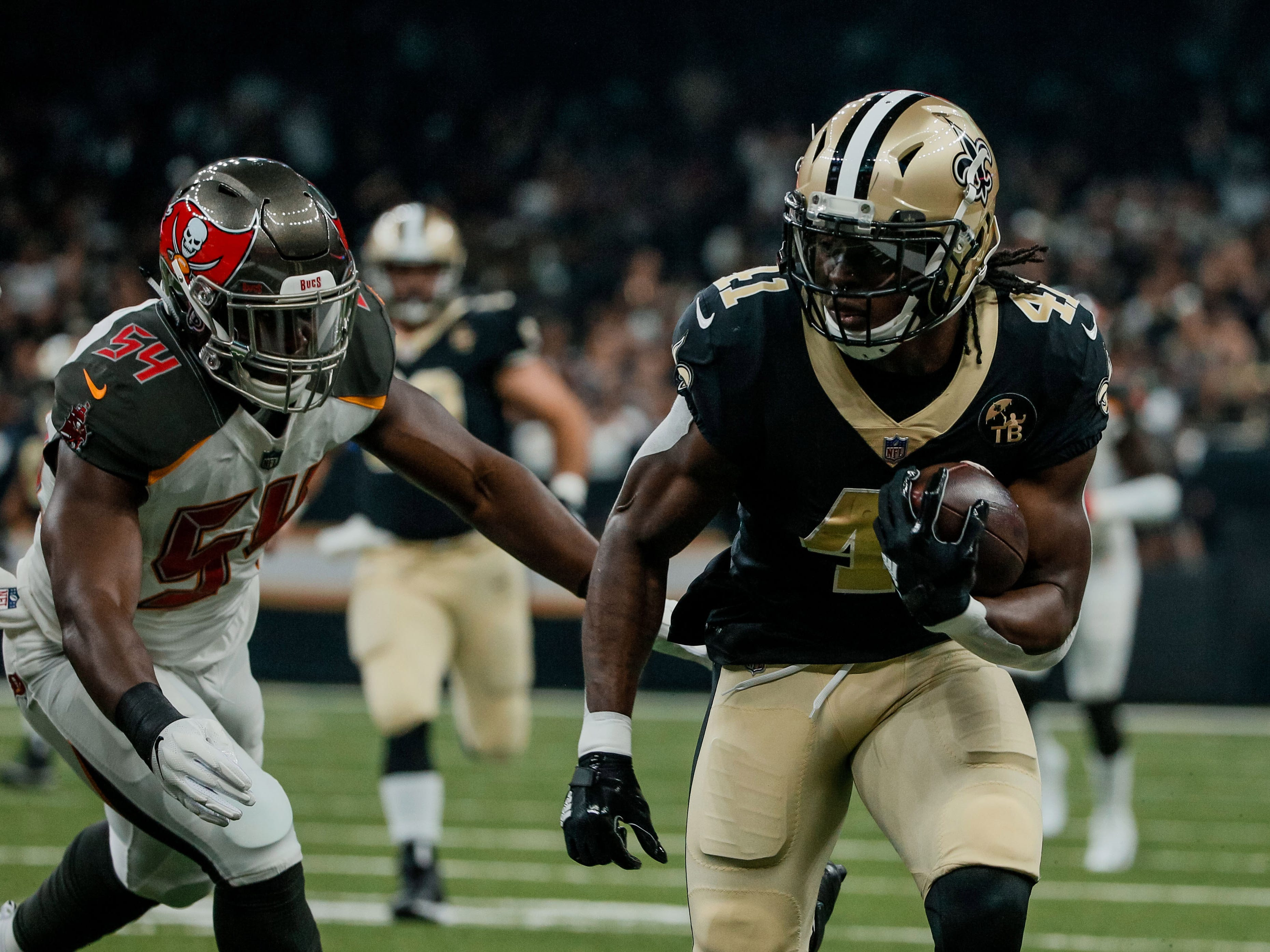 New Orleans Saints running back Alvin Kamara (runs past Tampa Bay Buccaneers linebacker Lavonte David during the first quarter of a game at the Mercedes-Benz Superdome.