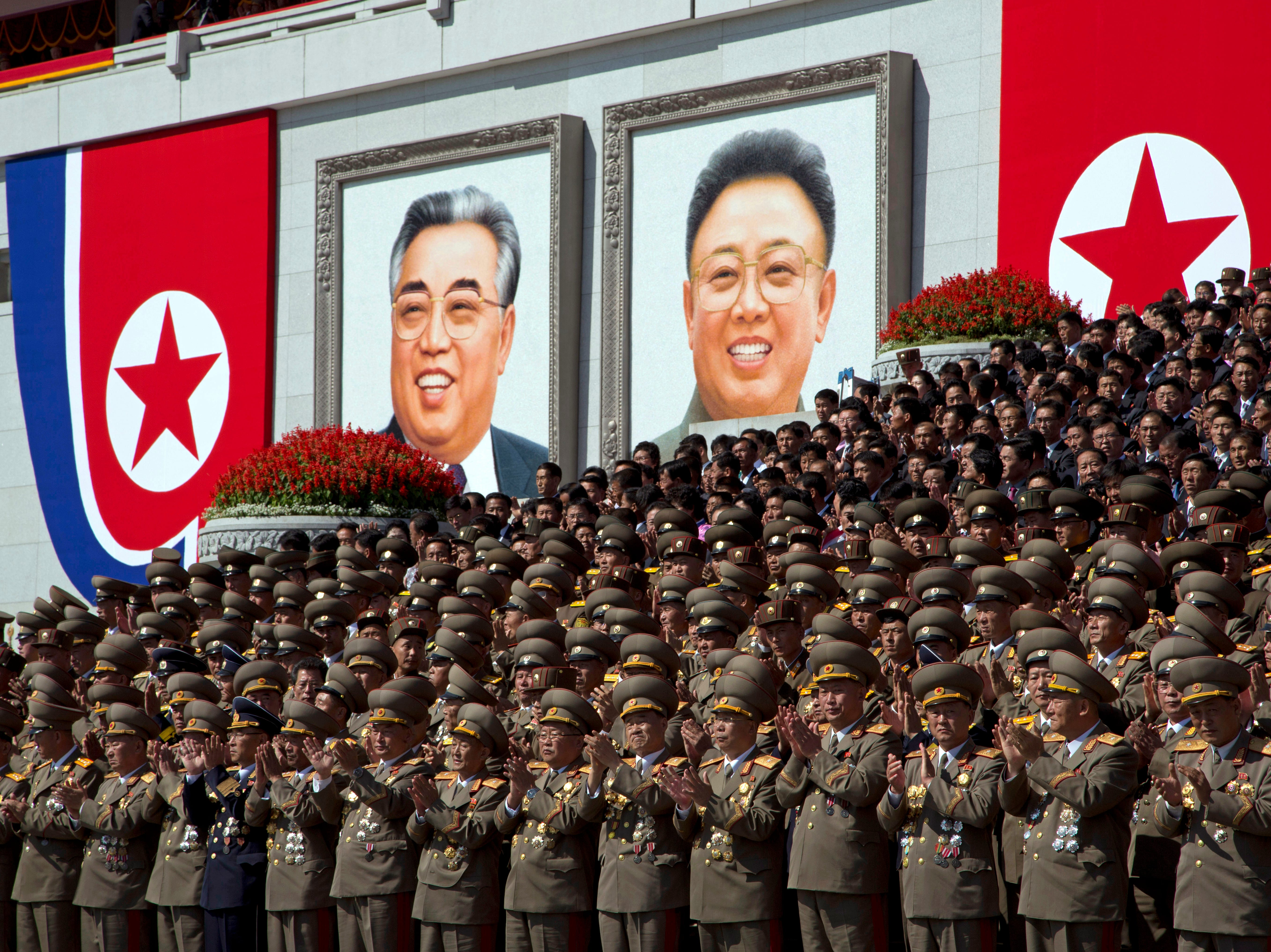 North Korean military officers applaud near portraits of late North Korean leaders Kim Il Sung and Kim Jong Il during a parade for the 70th anniversary of North Korea's founding day in Pyongyang, North Korea, Sunday, Sept. 9, 2018. North Korea staged a major military parade, huge rallies and will revive its iconic mass games on Sunday to mark its 70th anniversary as a nation.