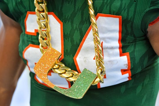 Nov 18, 2017; Miami Gardens, FL, USA; Miami Hurricanes running back Travis Homer (24) celebrates while wearing the turnover chain after recovering a fumble Virginia Cavaliers during the first half at Hard Rock Stadium. Mandatory Credit: Jasen Vinlove-USA TODAY Sports
