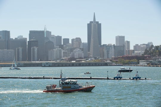 The Ocean Cleanup, an ocean cleaning system, moves through the San Francisco Bay as it heads toward the Pacific Ocean for testing on Sept. 8. 2018. About 18 people, including engineers, marine biologists, oceanographers and staff, will stay with the system for about seven weeks on the same ship that's towing it into place.