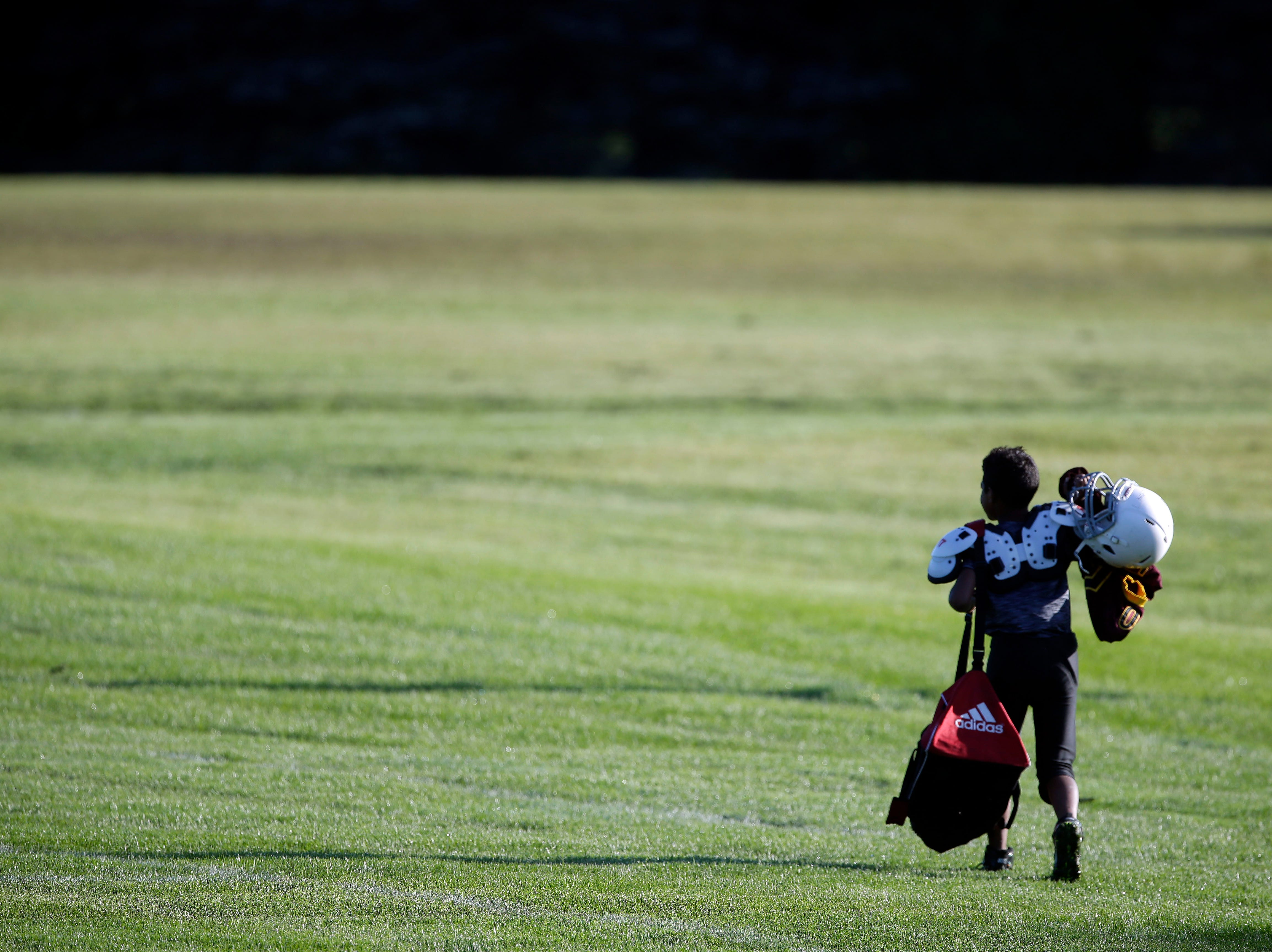 A player joins his team to warm-up as Fox Valley Pop Warner Football opens the season Saturday, September 8, 2018, at Plamann Park in Grand Chute, Wis.