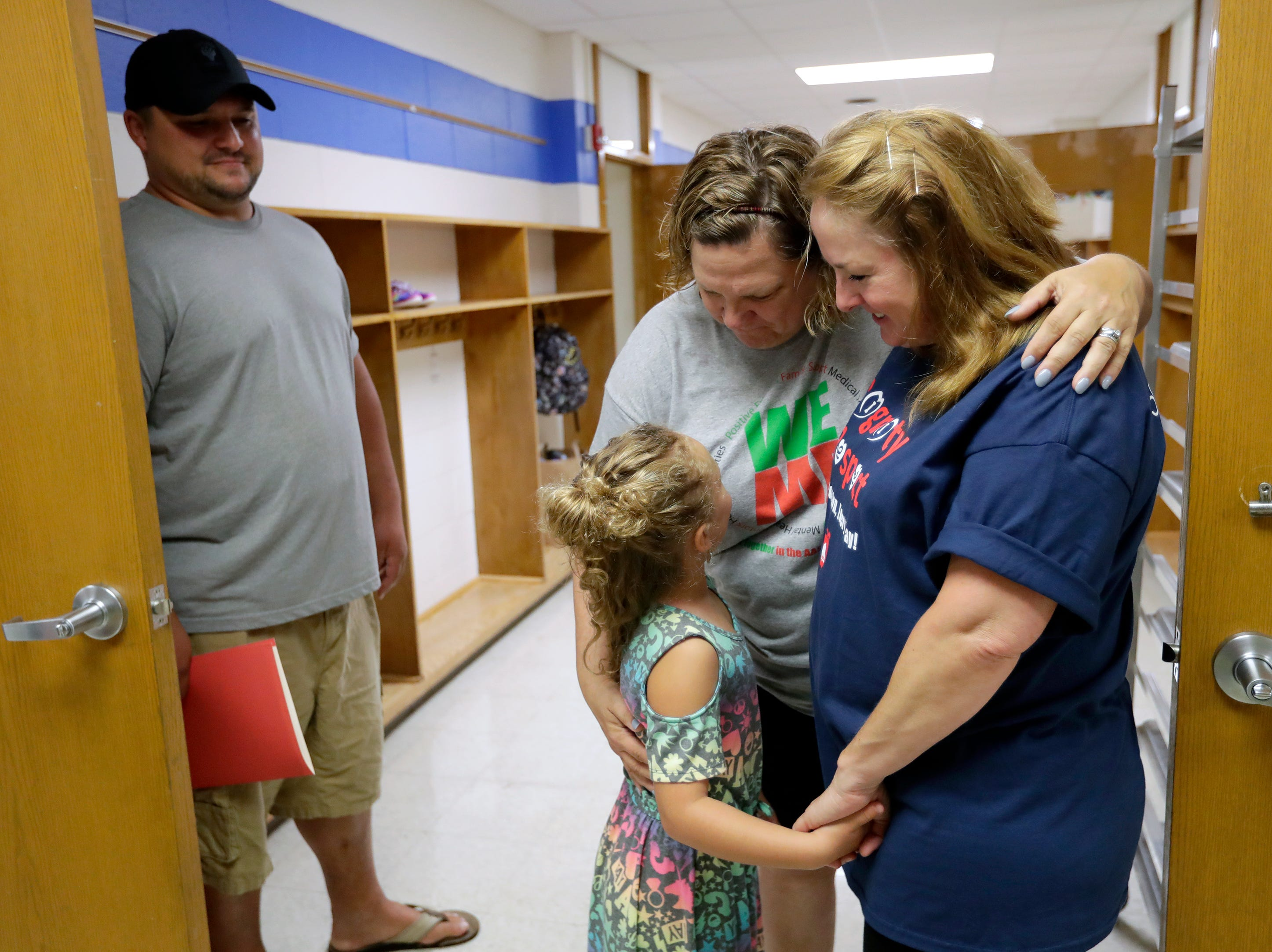 Ryan Merow, left, looks on as his daughter Reese, 6, is welcomed back to school by teachers Deb Hodson and Deb Tuttle, right, Tuesday, Sept. 4, 2018, at Badger Elementary School in Appleton, Wis. 