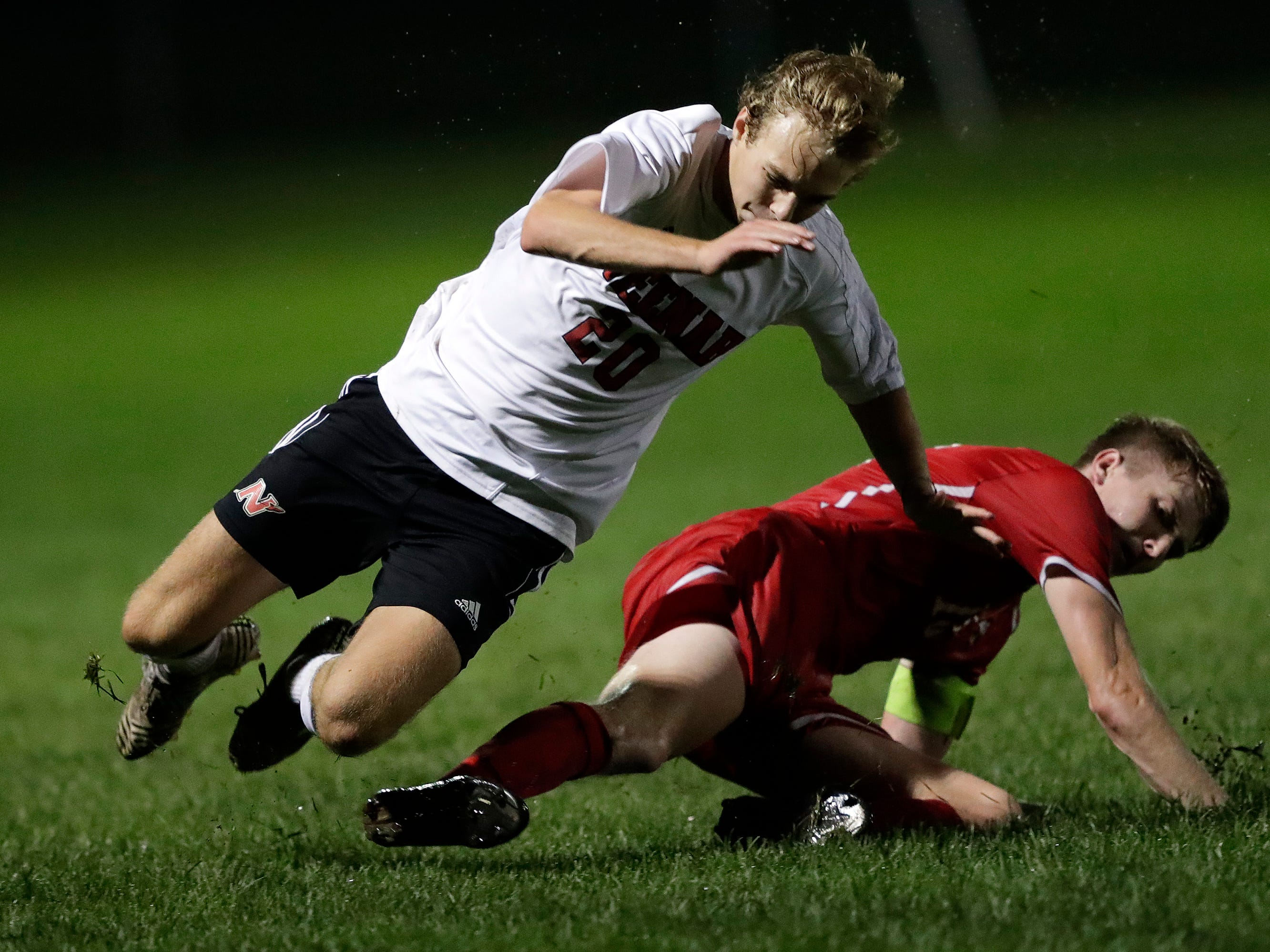 Neenah High School's Gabe Alexander (20) is tackled by Kimberly High School's Parker Schimmers (13) during their boys soccer game Tuesday, Sept. 4, 2018, at Papermaker Field in Kimberly, Wis. 