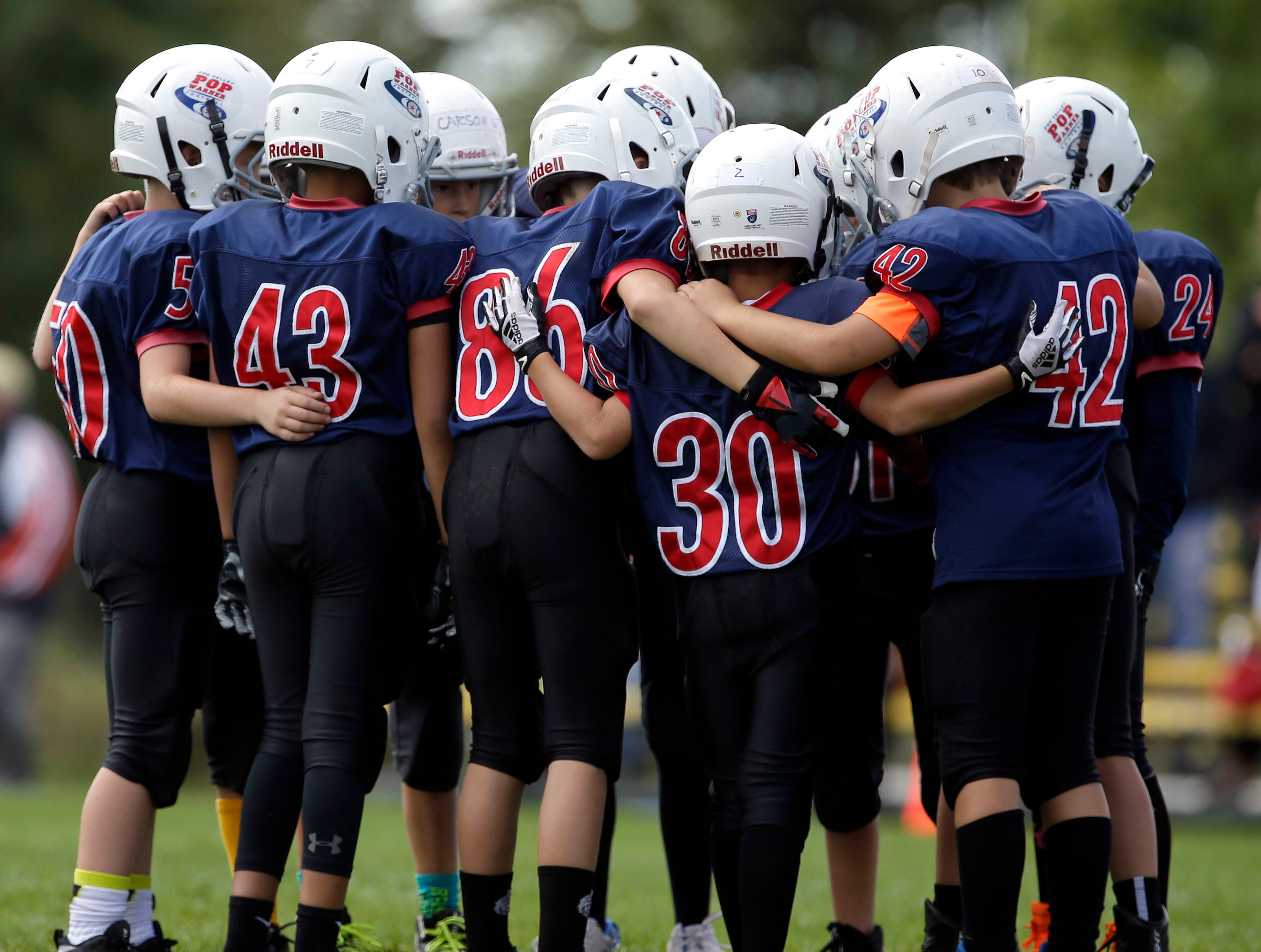 The Patriots huddle during a game against the Rockets as Fox Valley Pop Warner Football opens the season Saturday, September 8, 2018, at Plamann Park in Grand Chute, Wis.